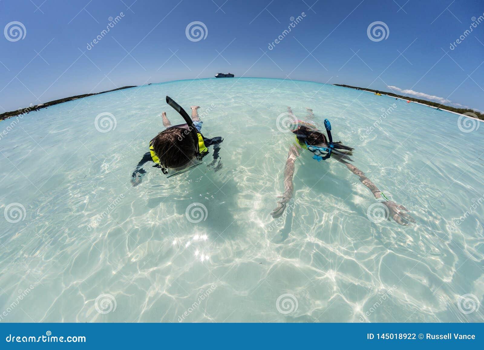 潜航在与游轮的透明的水中的少女和男孩在与广角弯曲的天际的背景中