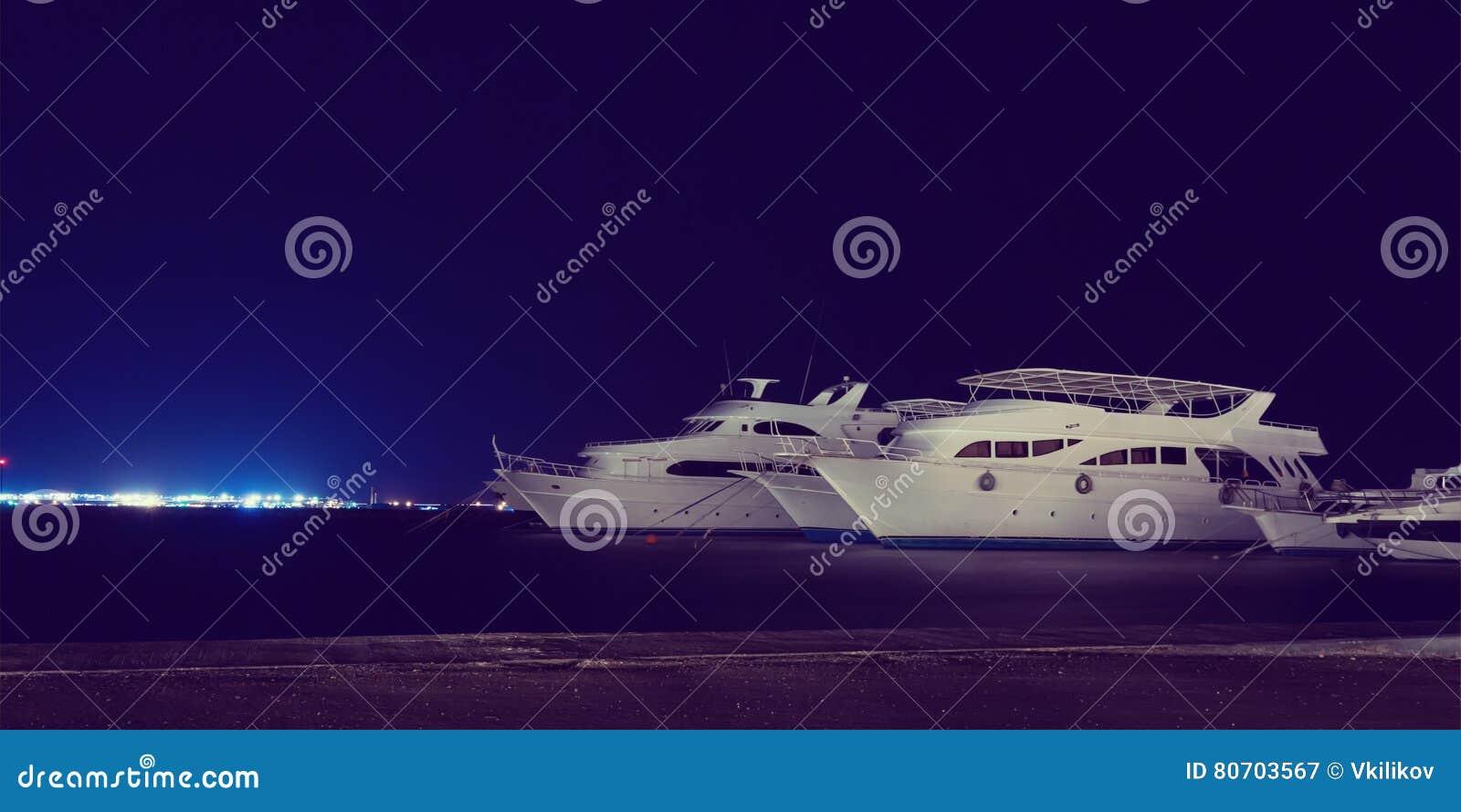 潜水巡航游艇在夜小游艇船坞,减速火箭的样式停泊了