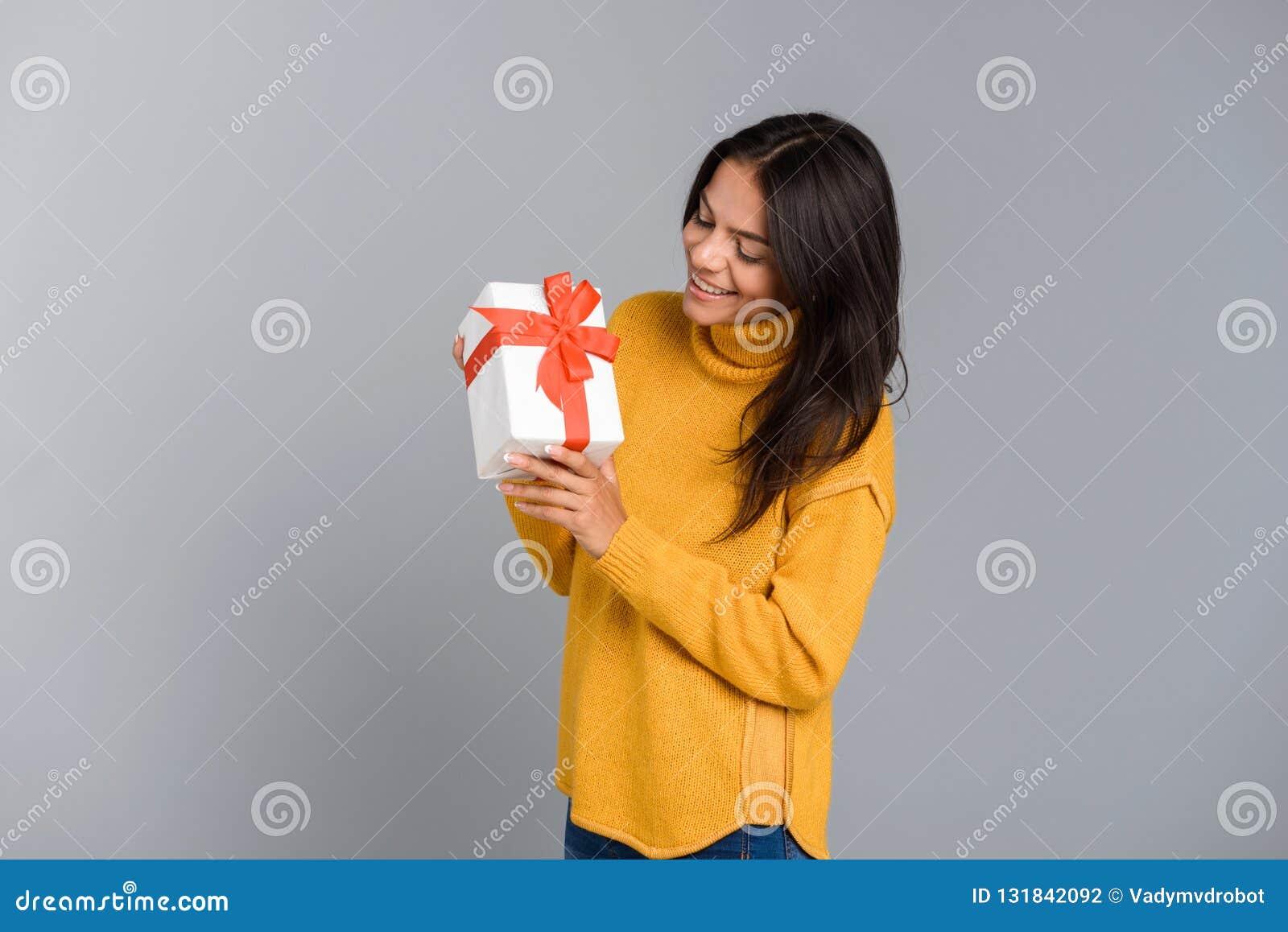 激动妇女摆在被隔绝在灰色墙壁背景藏品箱子惊奇礼物
