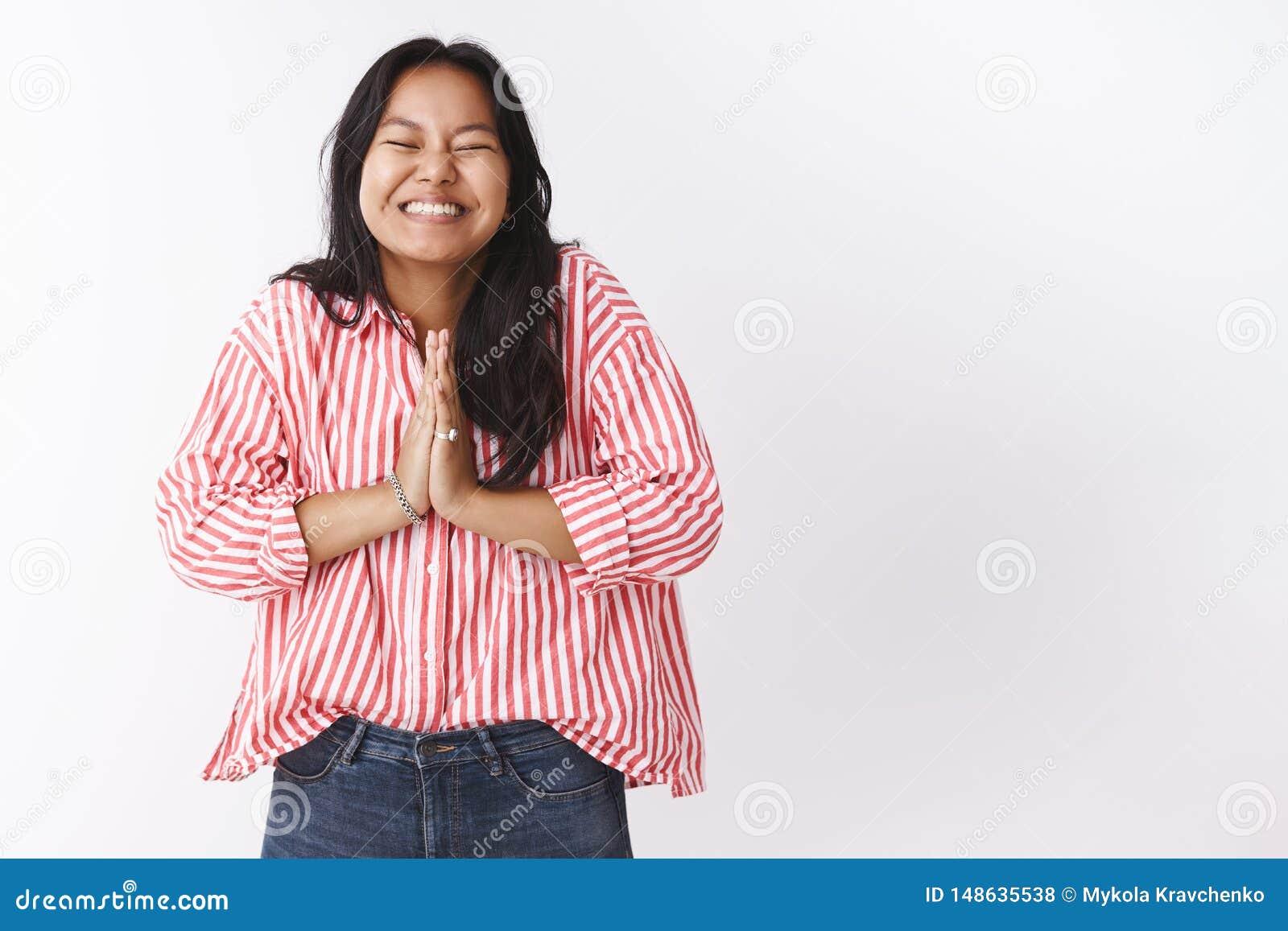激动的女孩不可能等待愿望实现的微笑快乐与握手在的闭合的眼睛祈祷,棕榈一起按了