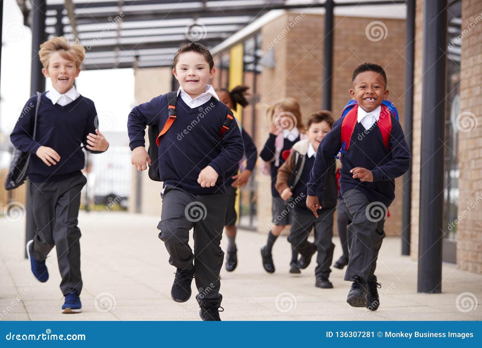 激动的小学孩子,佩带的校服和背包,运行在他们的教学楼之外的一个走道,正面图