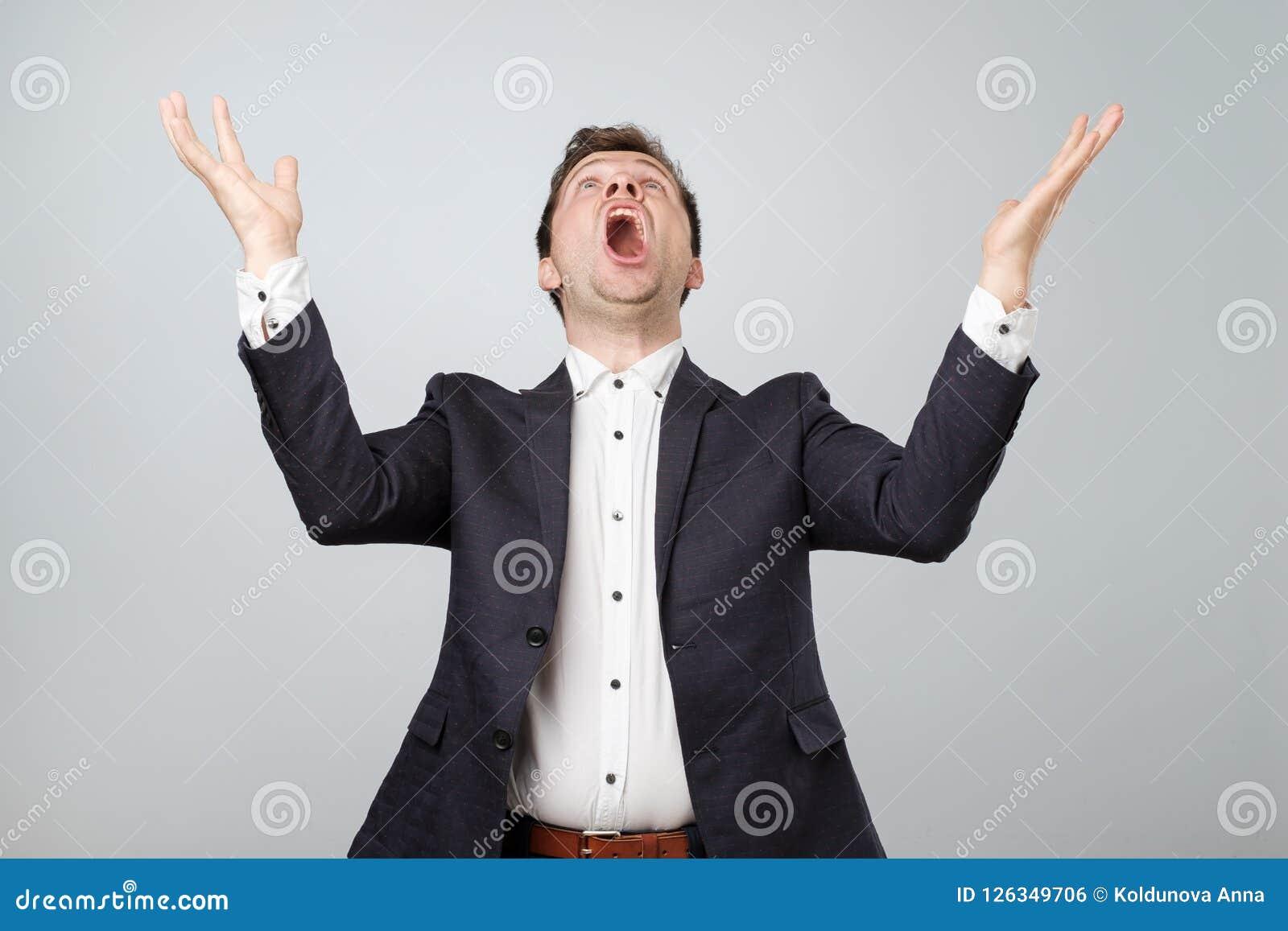 激动的年轻男性画象在衣服的尖叫在停滞手的震动和触目惊心