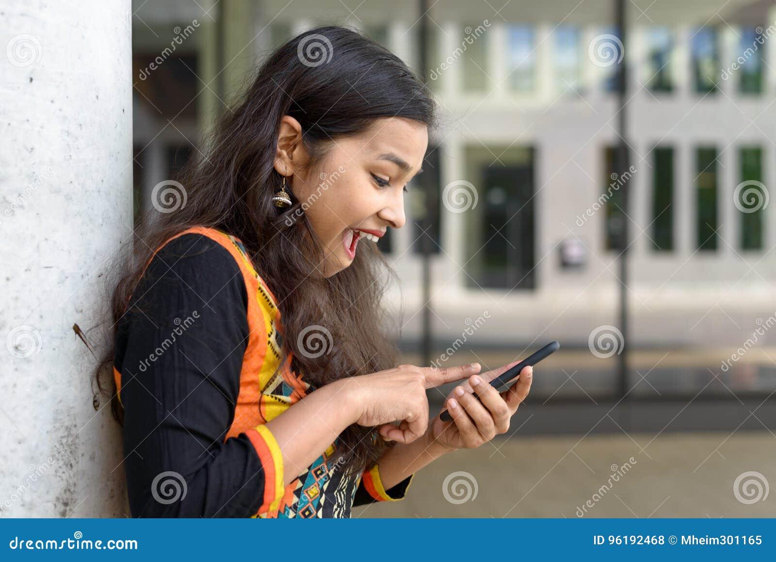 激动的年轻印地安女孩惊叹在sms