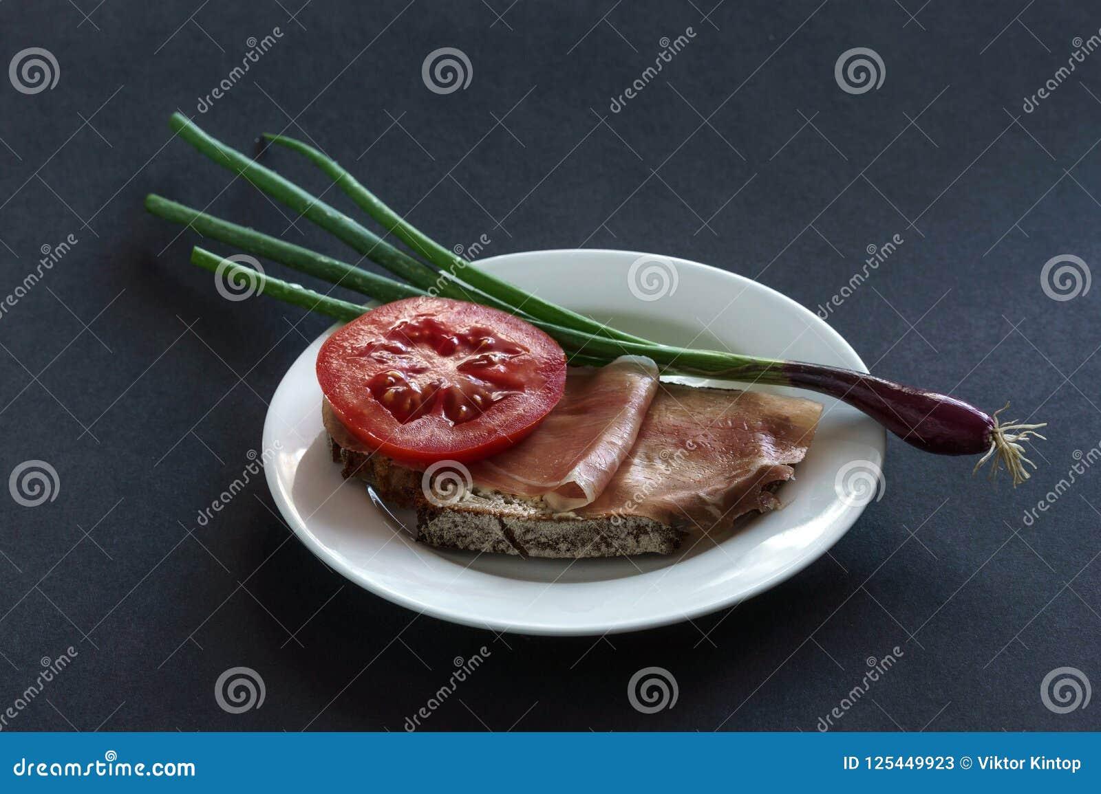 火腿面包用蕃茄和韭葱在板材,灰色背景