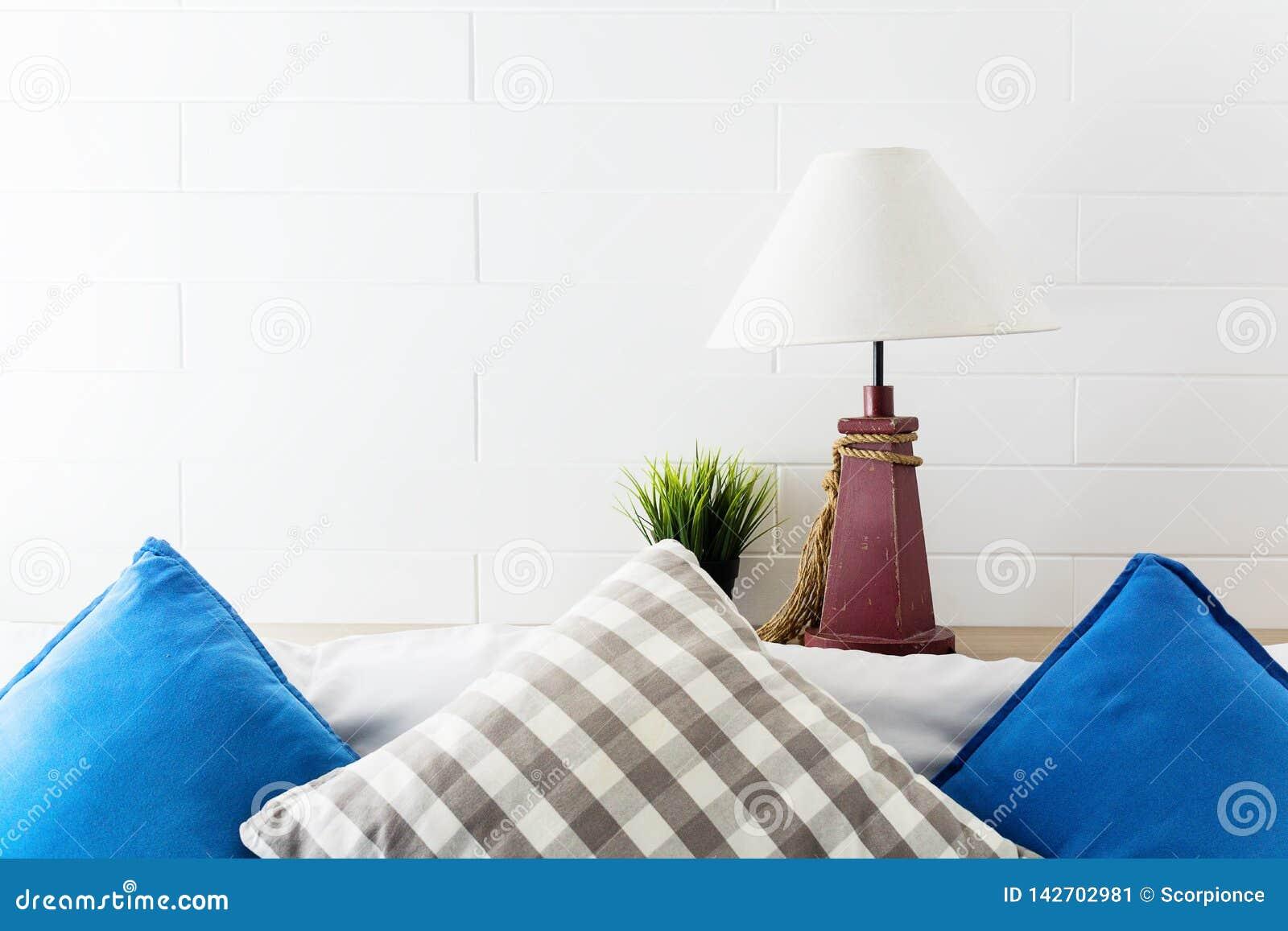 灯和绿色植物床边的有蓝色和灰色pollows的 酒店房间内部背景