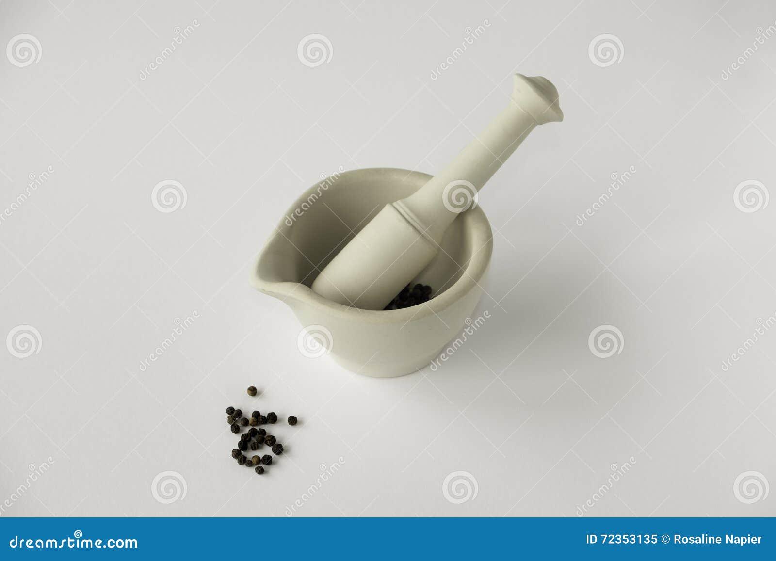 灰浆和杵用黑干胡椒在简单的白色backgrou