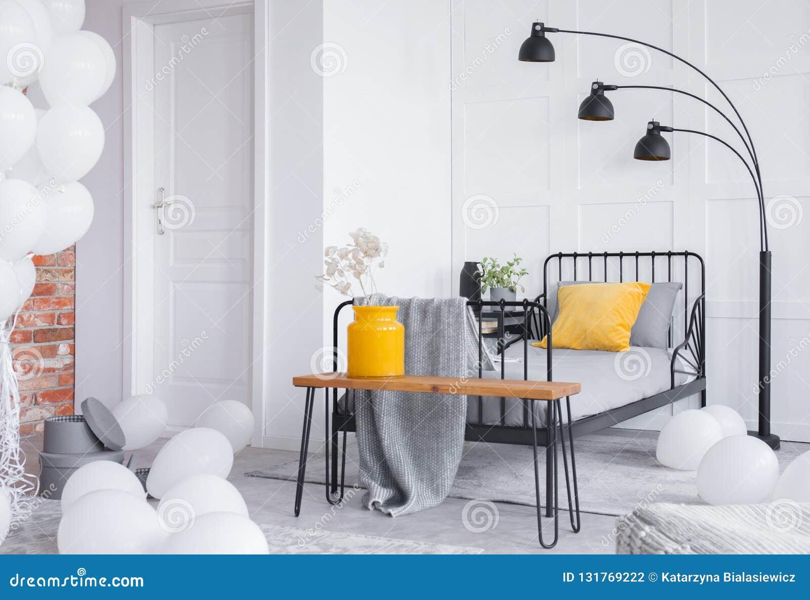 灰色床和黄色花瓶有白花的在长木凳在时髦的工业卧室