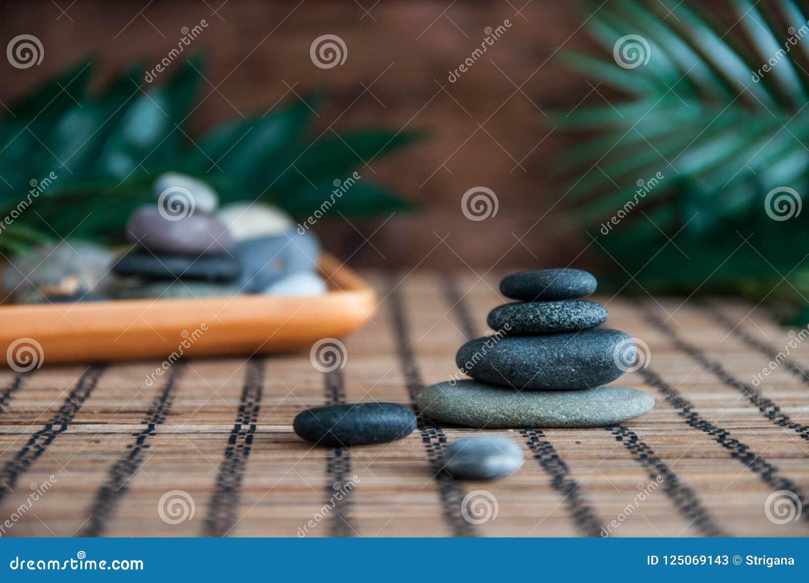 灰色禅宗石头金字塔与绿色叶子和菩萨雕象的 和谐、平衡和凝思,温泉,按摩的概念,放松