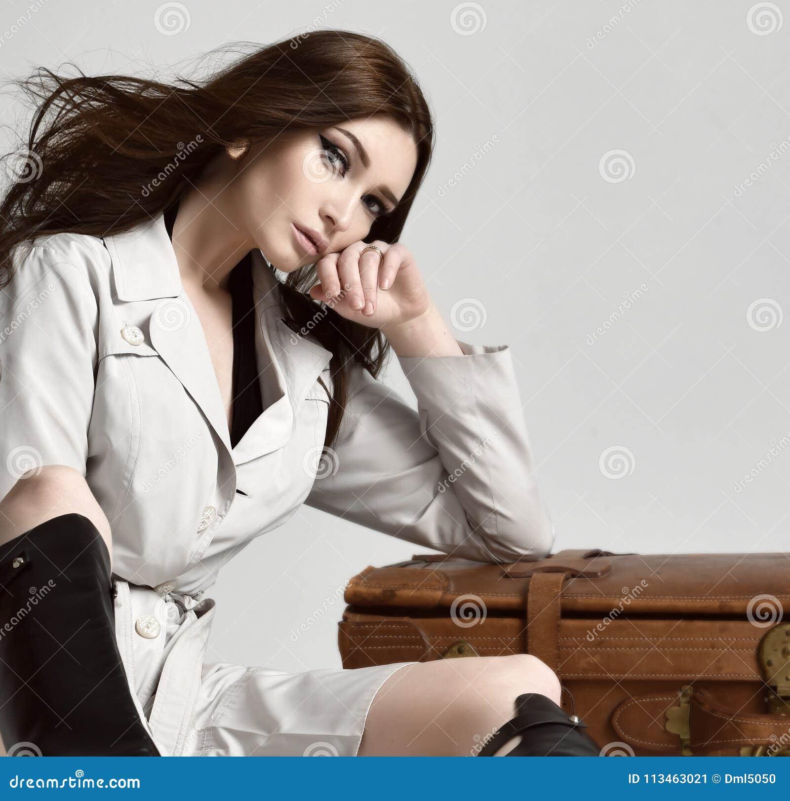 灰色秋天夹克的美丽的深色的行家妇女有坐在皮革棕色减速火箭的旅行袋子附近的有风头发的