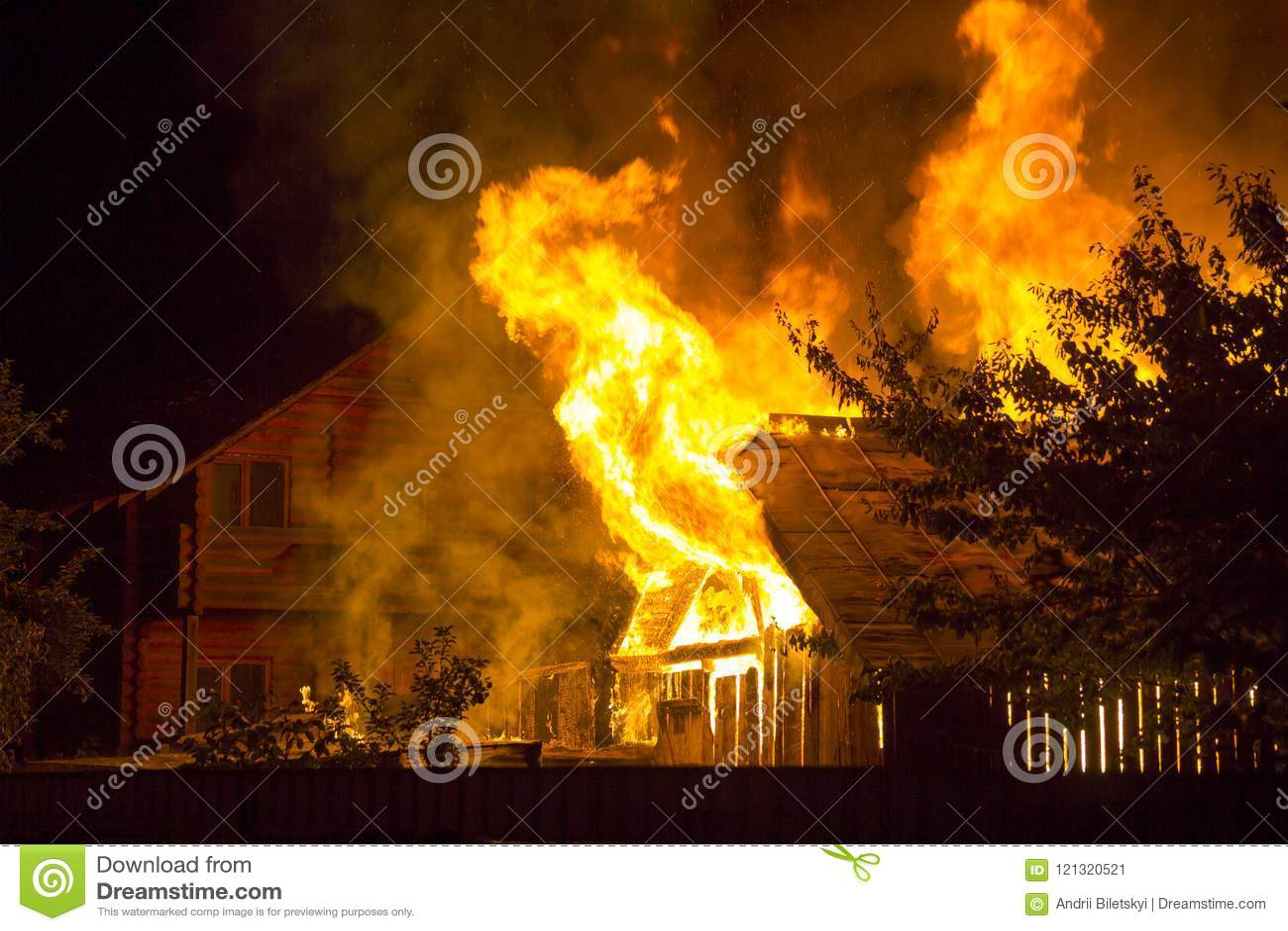 灼烧的木房子在晚上 明亮的橙色火焰和浓烟从铺磁砖的屋顶下面在黑暗的天空、树剪影和r