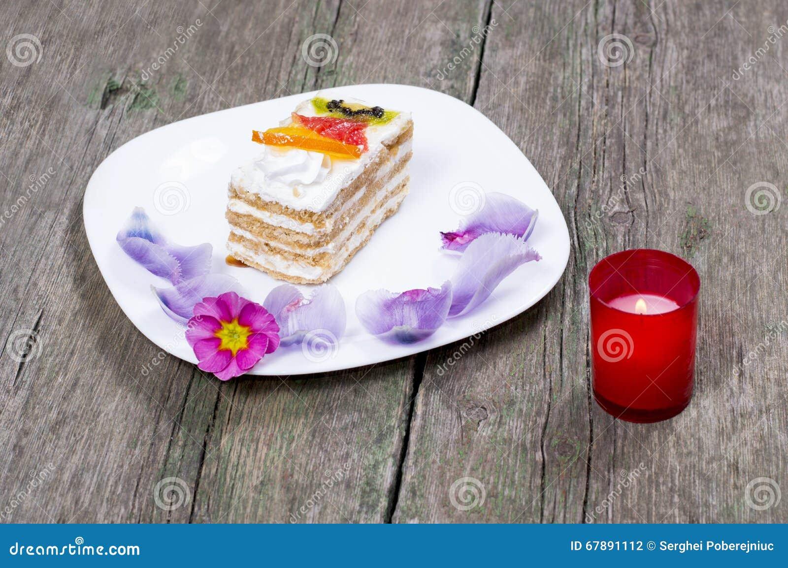 灼烧的蜡烛和板材有用花装饰的蛋糕的