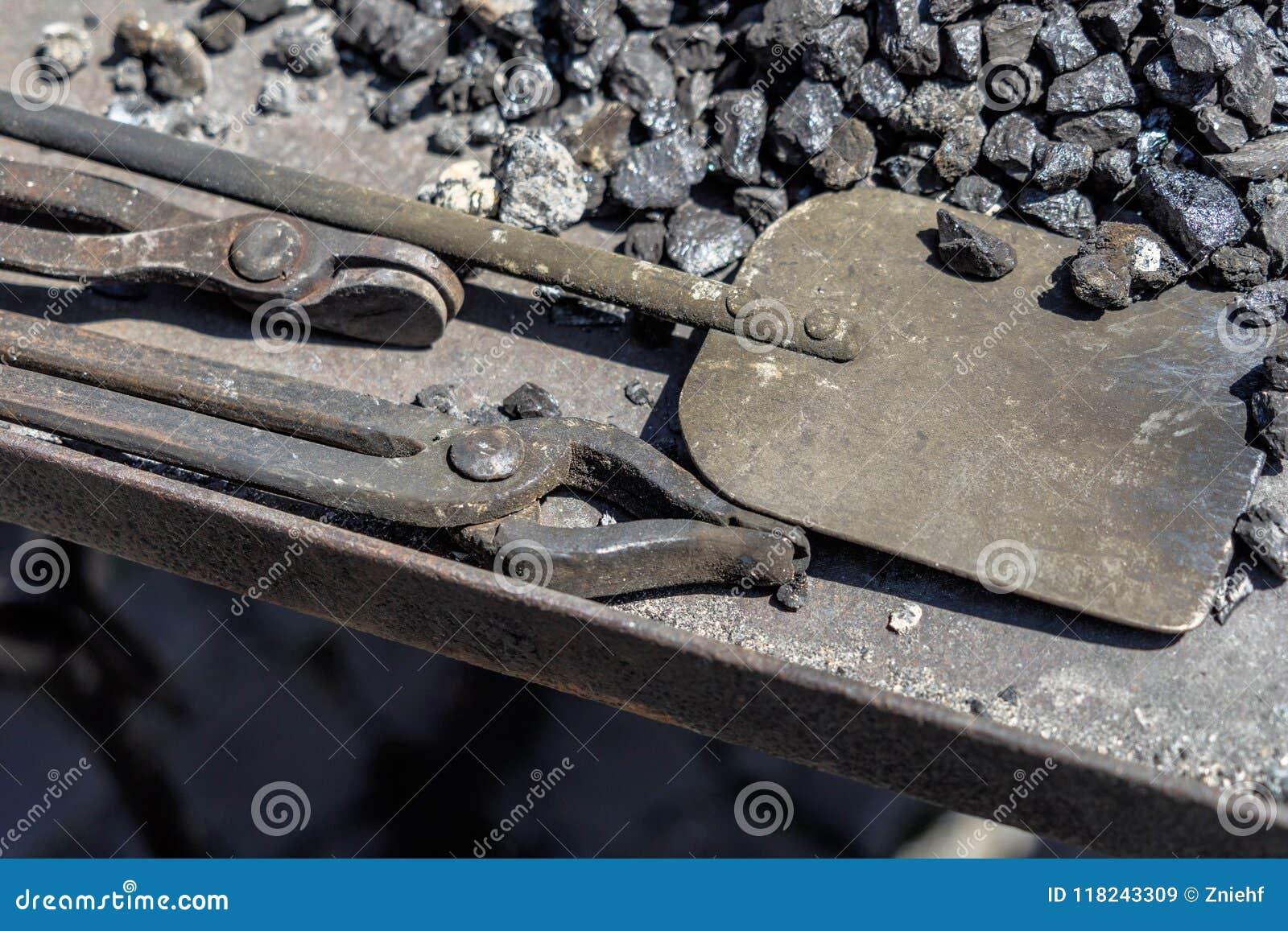 炭烬和铁锹的钳子从中世纪伪造的煤炭的