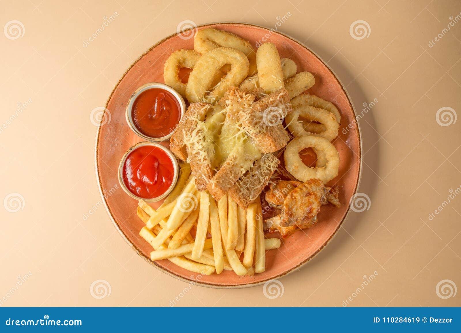 炸薯条,洋葱圈,鸡翼,面包干,对啤酒的一顿快餐在一块大板材用在棕色背景的两个调味汁 顶视图