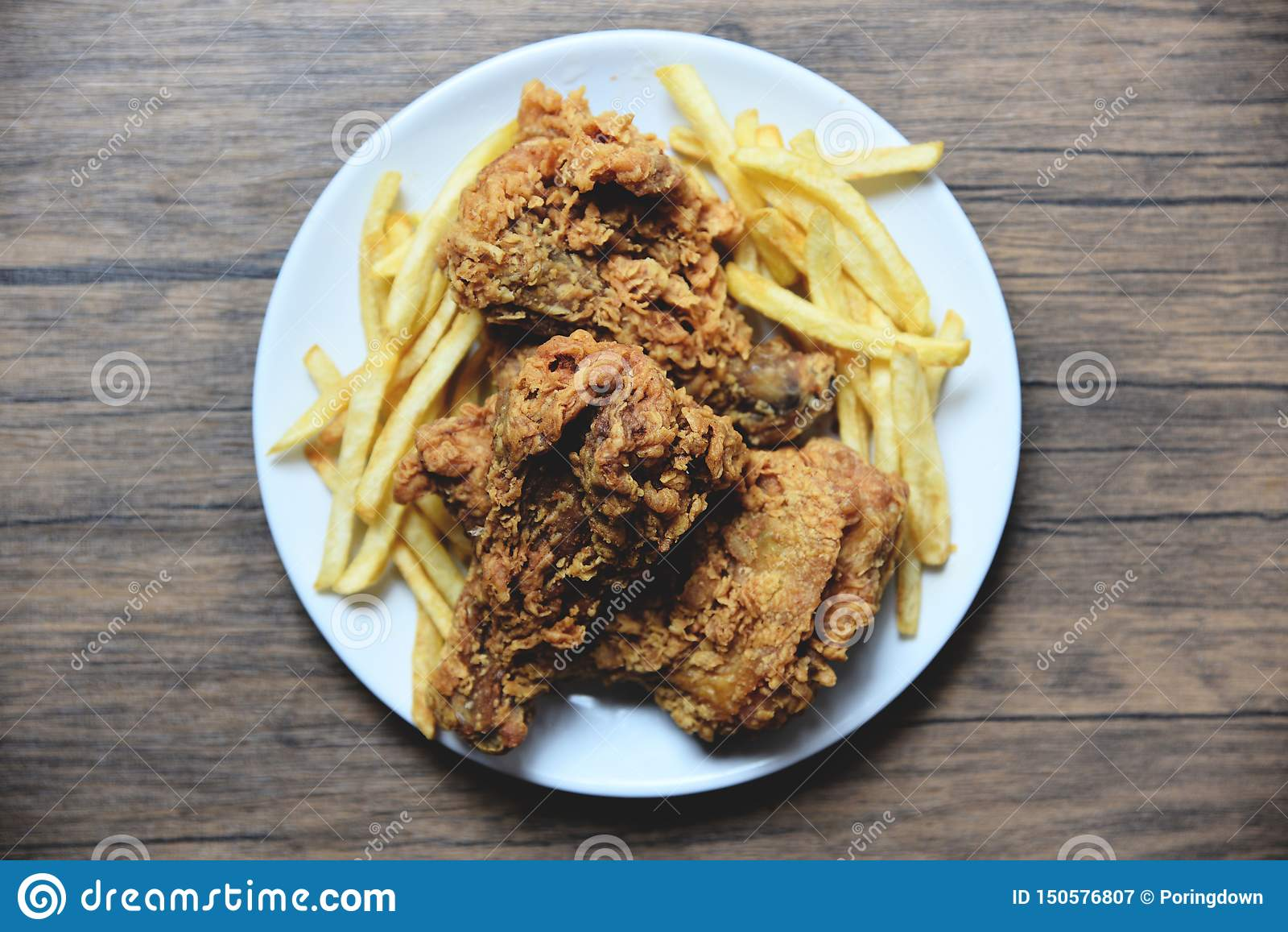 炸鸡酥脆在有薯条的白色板材在饭桌
