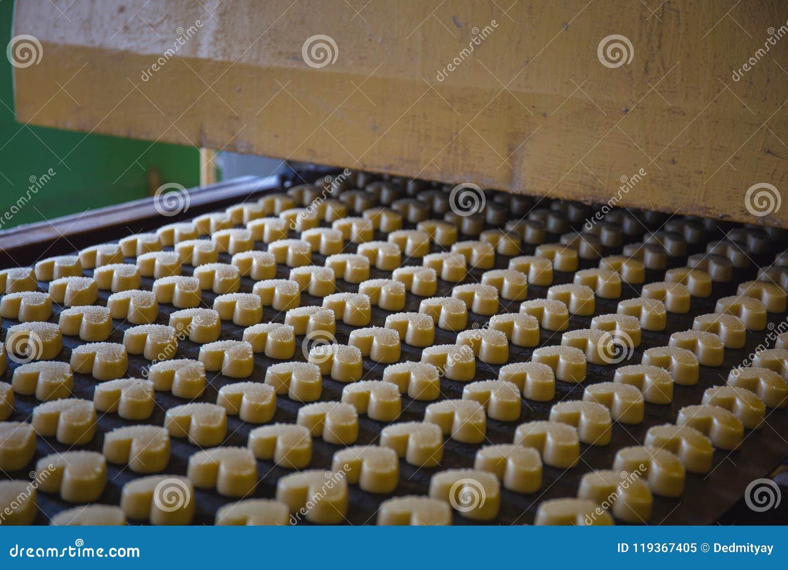 烘烤生产线在曲奇饼工厂 未煮过的饼干以心脏的形式在传送带的
