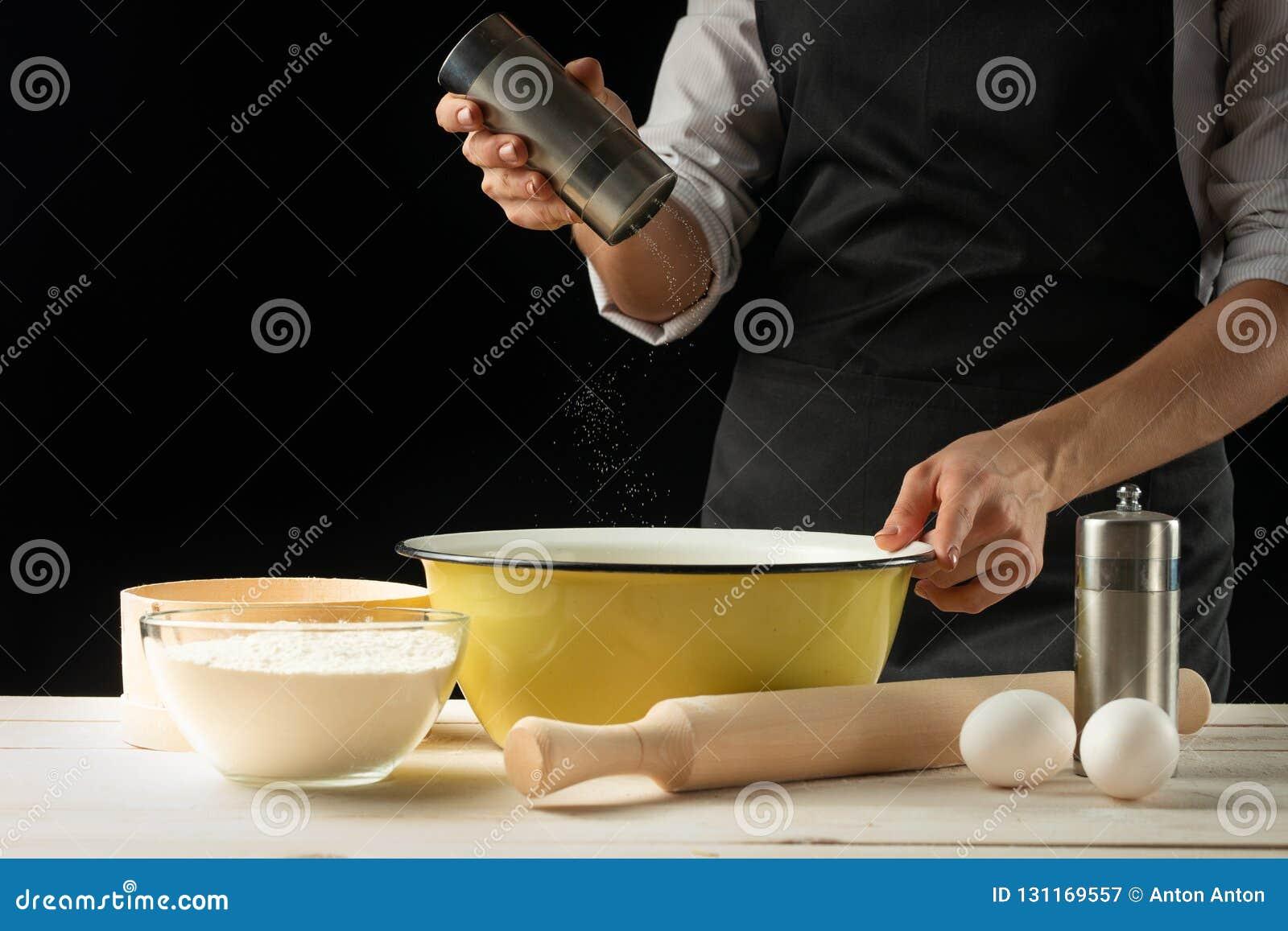 烘烤 供以人员准备面包、复活节蛋糕、复活节面包或者跨小圆面包在木桌上在面包店关闭  准备面包窦的人