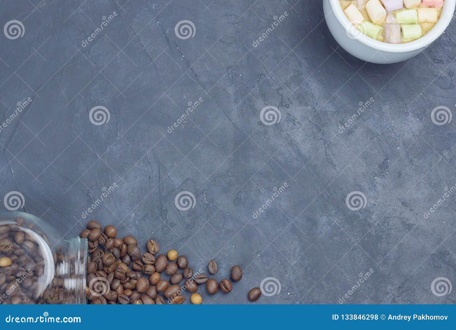 烤咖啡豆,倒从有一杯白色咖啡的一个玻璃瓶子和蛋白软糖 有角安置