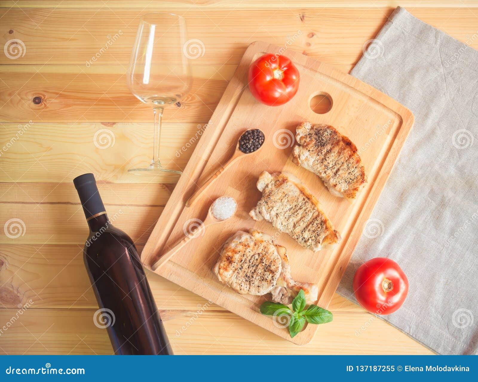 烤在切板、瓶红酒和空的酒杯的猪肉牛排
