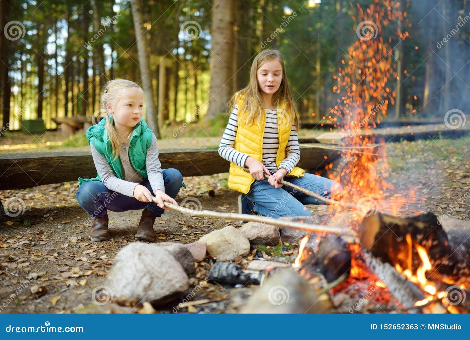 烤在棍子的逗人喜爱的年轻姐妹热狗在篝火 孩子获得乐趣在阵营火 野营与孩子在秋天森林里