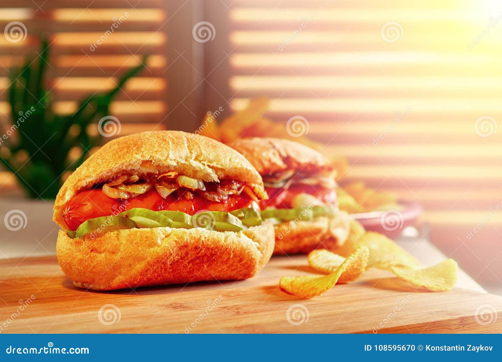 烤热狗或熏肉香肠用油煎的葱和用卤汁泡的黄瓜 筹码查出土豆白色 在木桌上的最后快餐