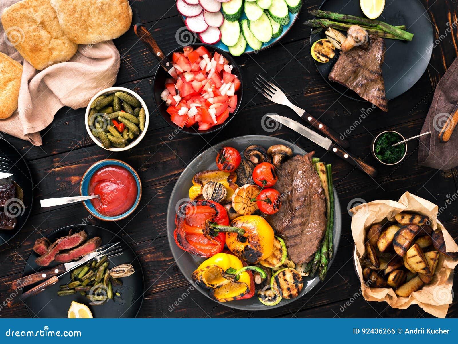烤牛排和烤菜在木桌上