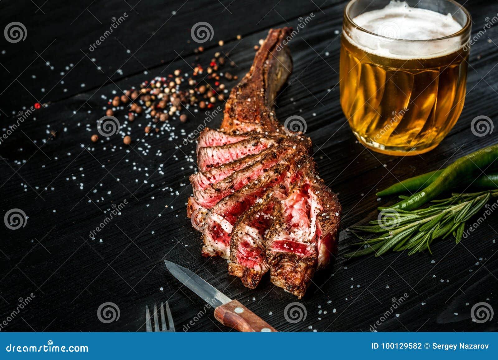 烤牛肉干燥年迈的肋骨用香料、菜和一杯在黑木背景的低度黄啤酒特写镜头