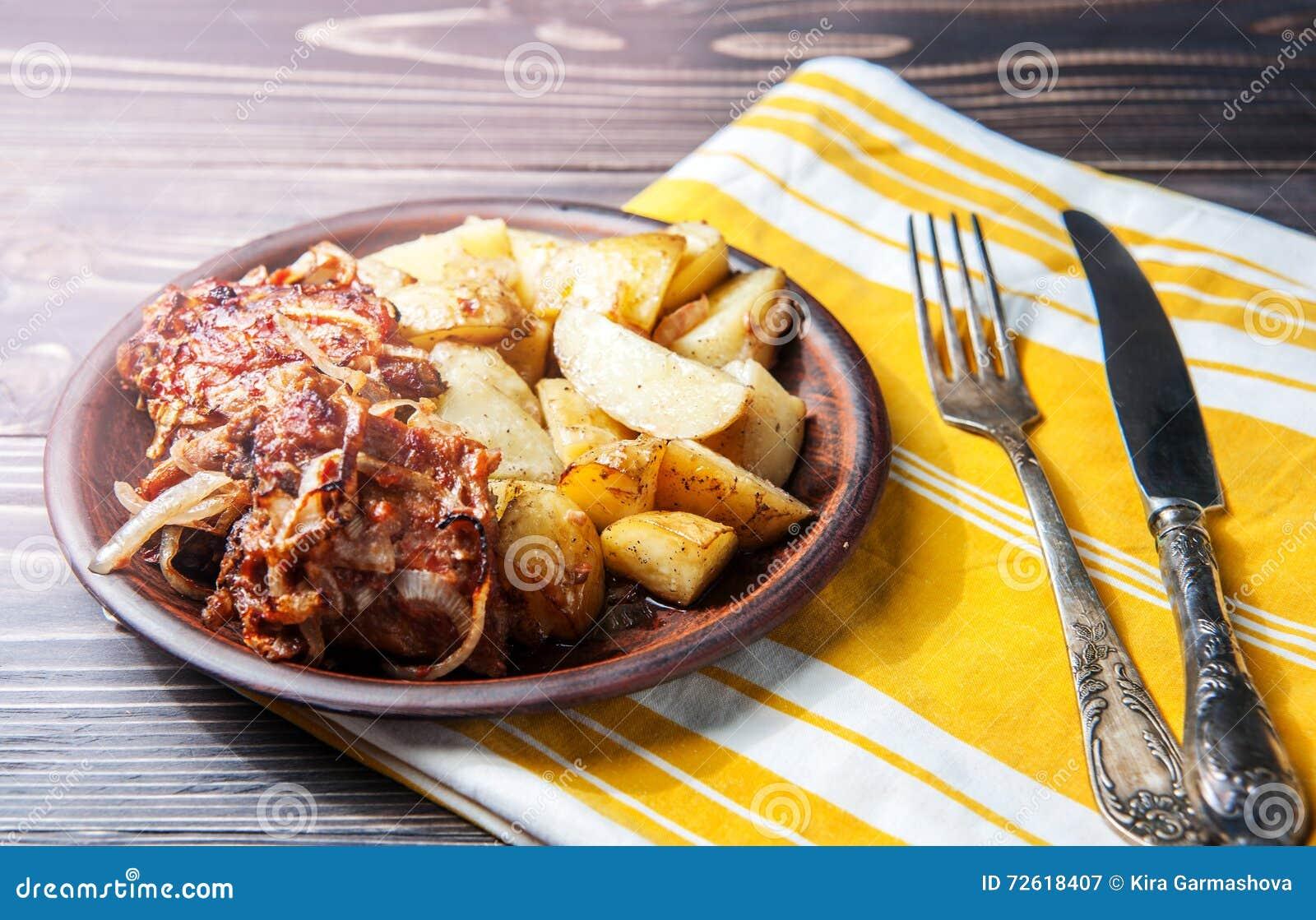 烤肋骨用烤肉汁、葱和热的酥脆土豆