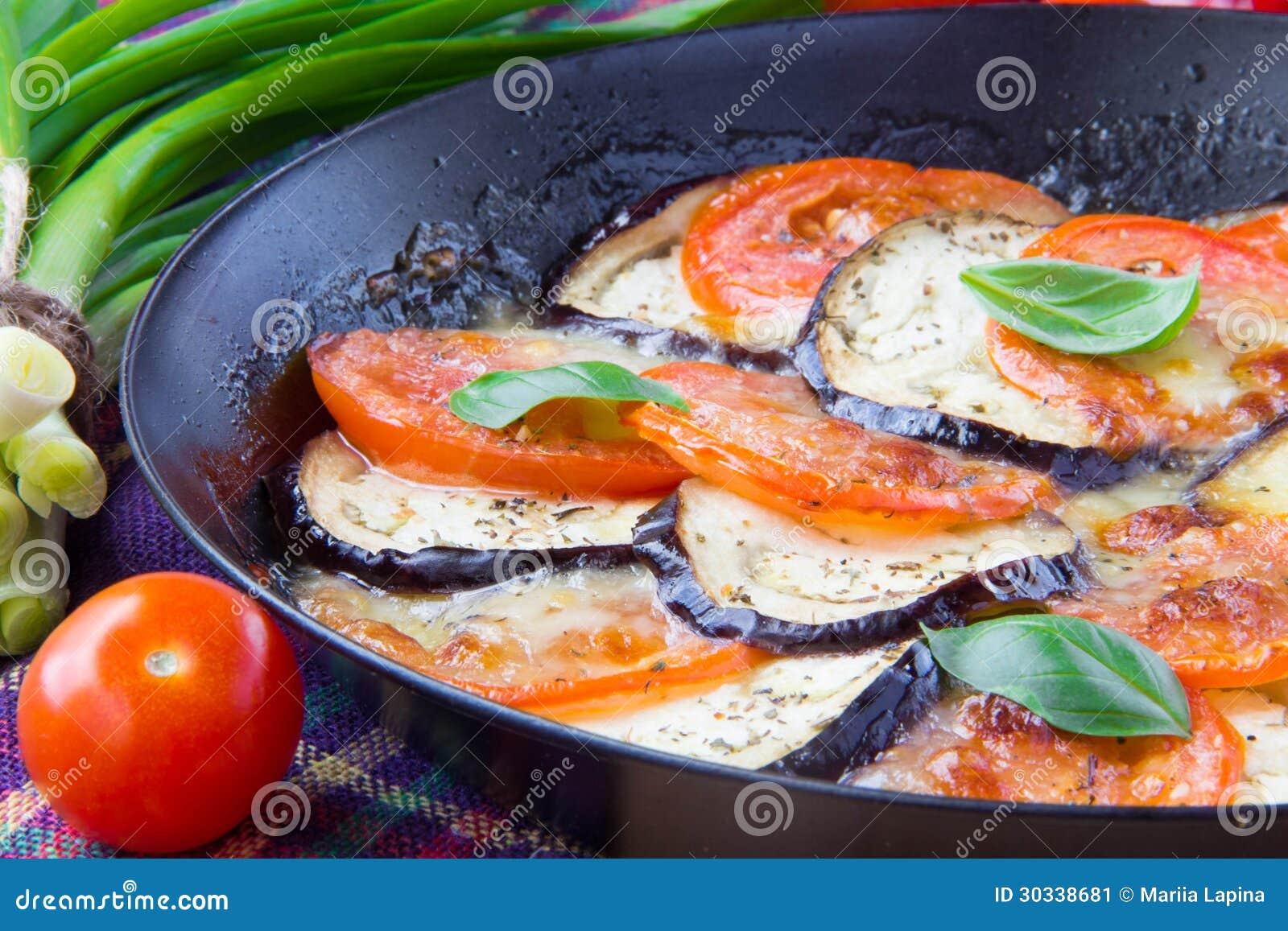 烤蕃茄、茄子和乳酪在平底锅有蓬蒿的