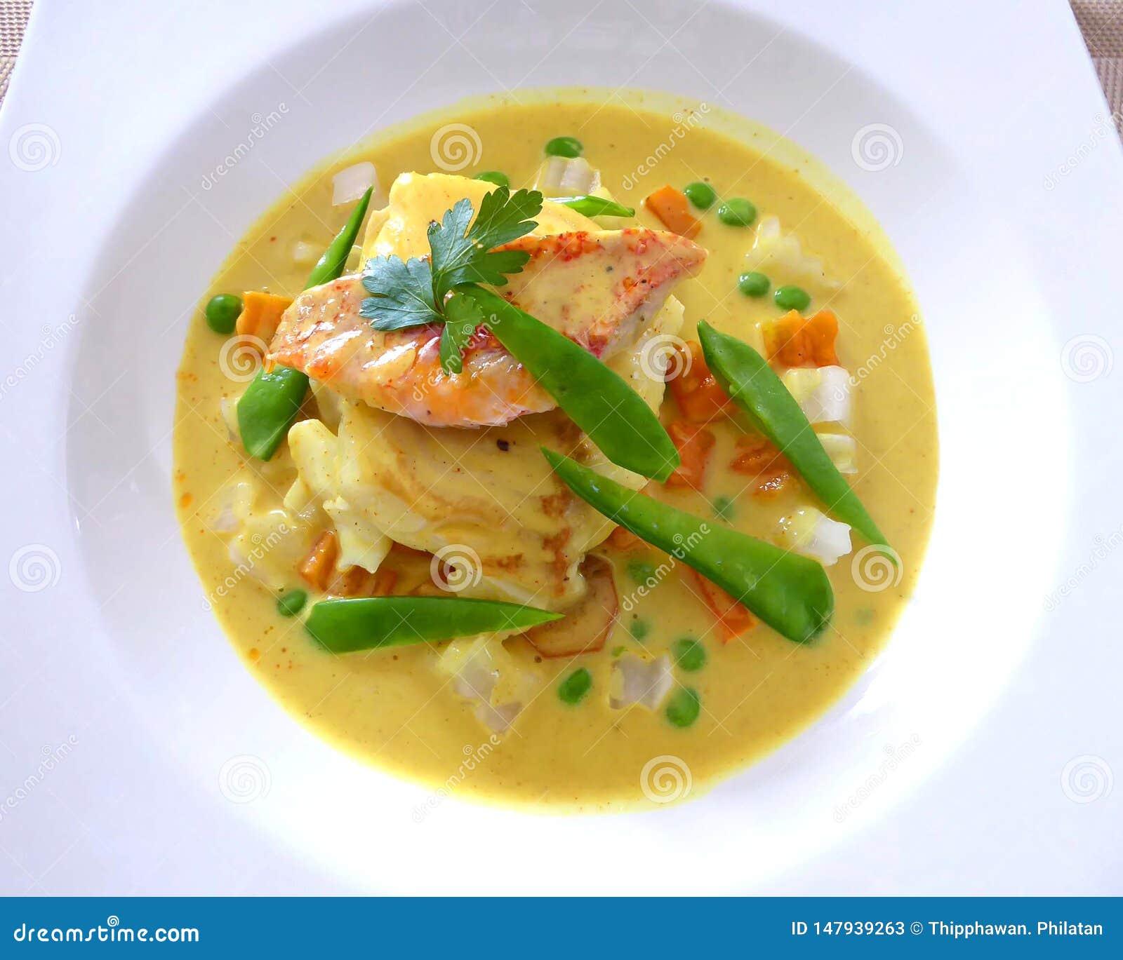 烤鱼用在白色隔绝的黄色咖喱汁