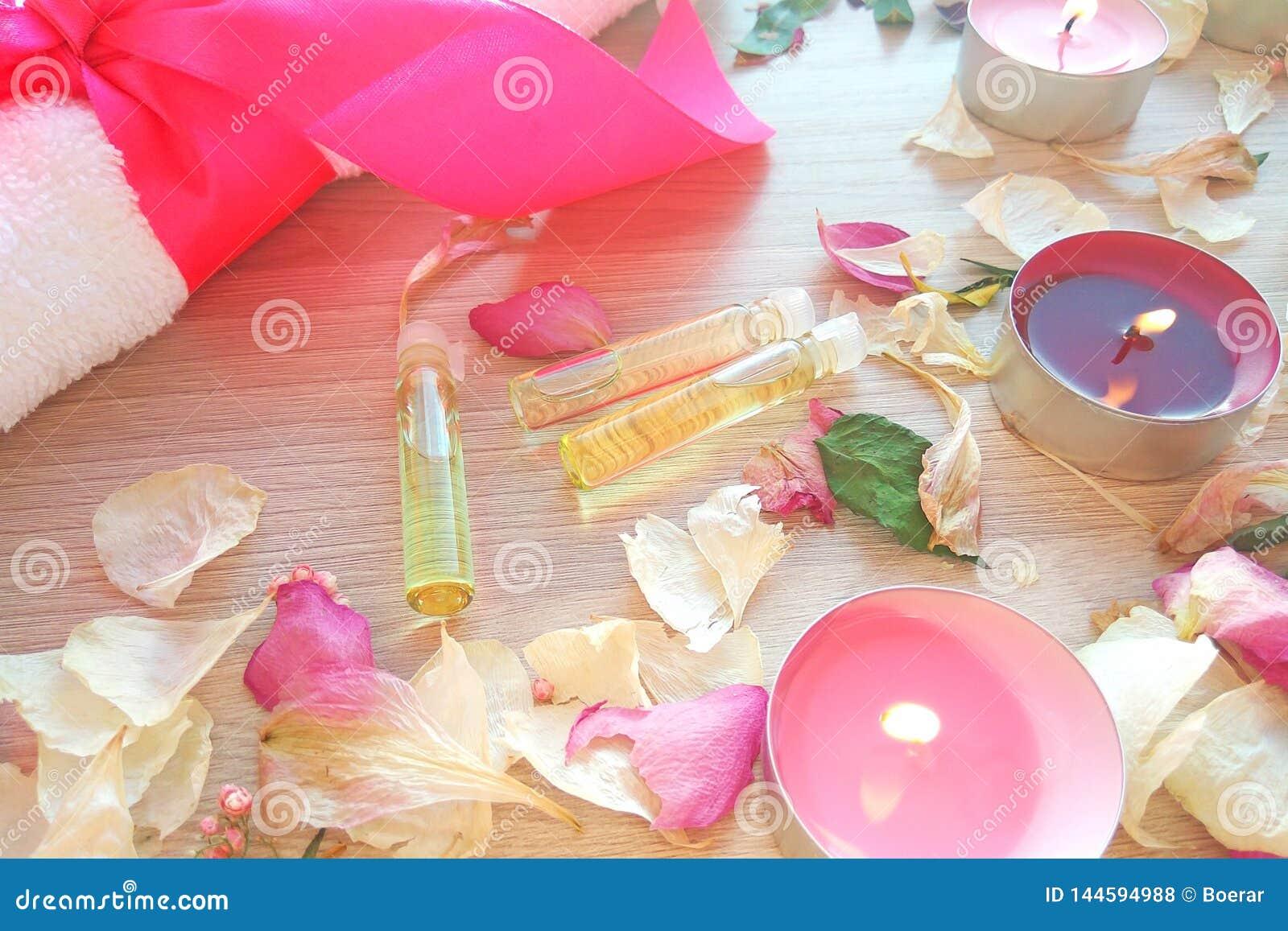 烧与根本温泉油的蜡烛,上升了花瓣和白色毛巾在木桌背景