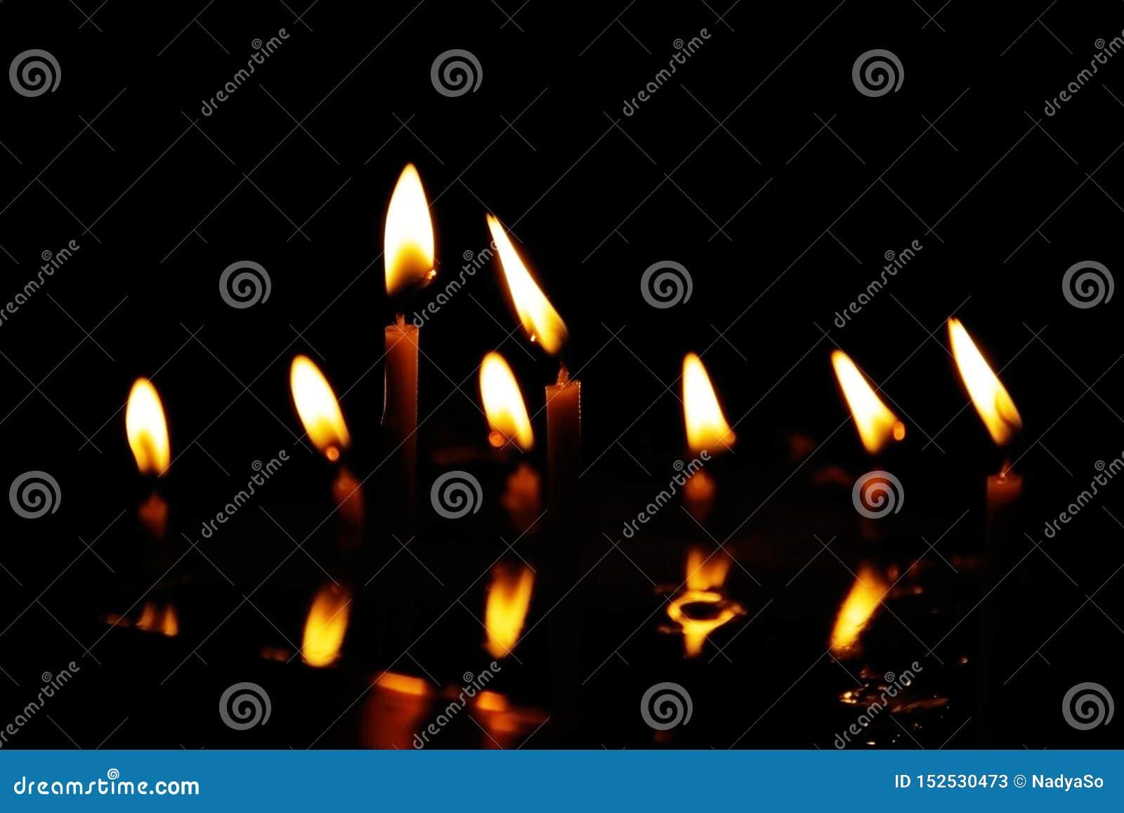 烧在寺庙的沈默黑暗中的祷告蜡烛,反映在水