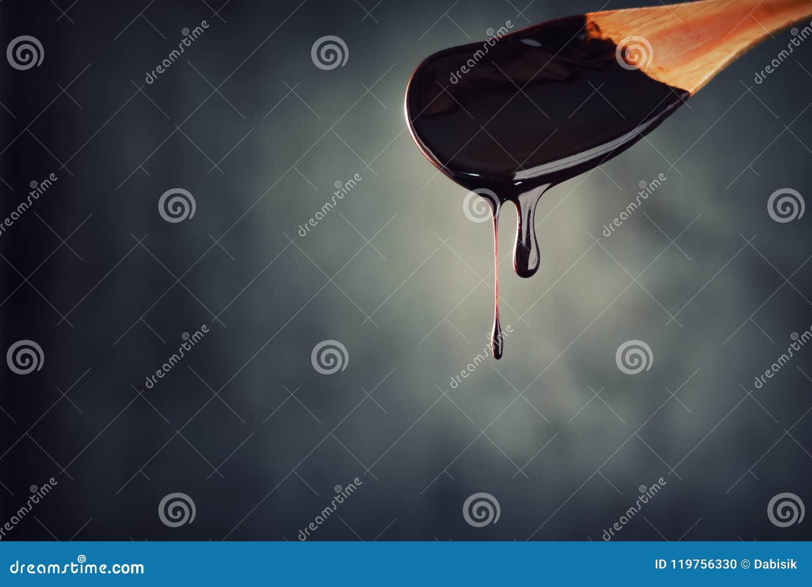 热巧克力喷气机从木匙子滴下在黑暗的背景