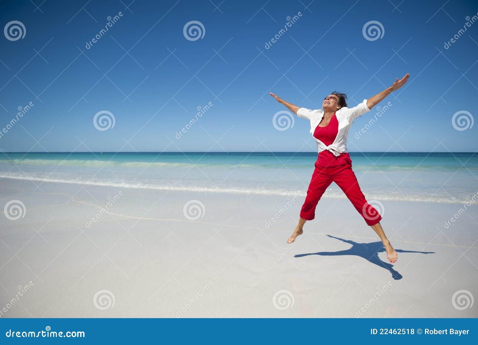热带海滩的愉快的成熟妇女