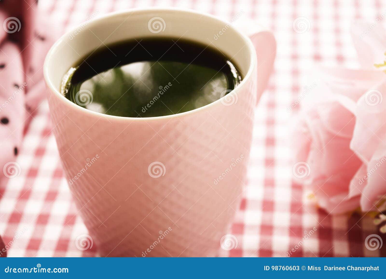 热的咖啡和新鲜的牛奶和甜桃红色玫瑰在桌上