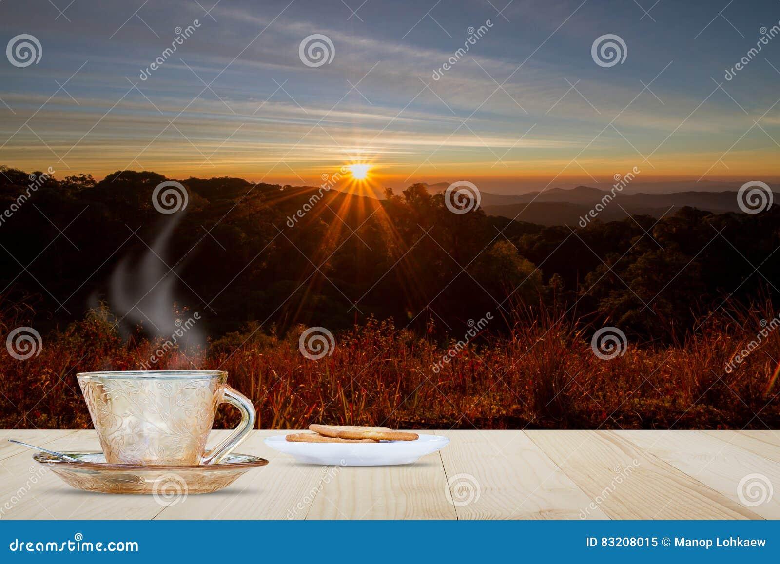 热的咖啡杯和饼干在木台式在被弄脏的草甸和山与日出和火光背景