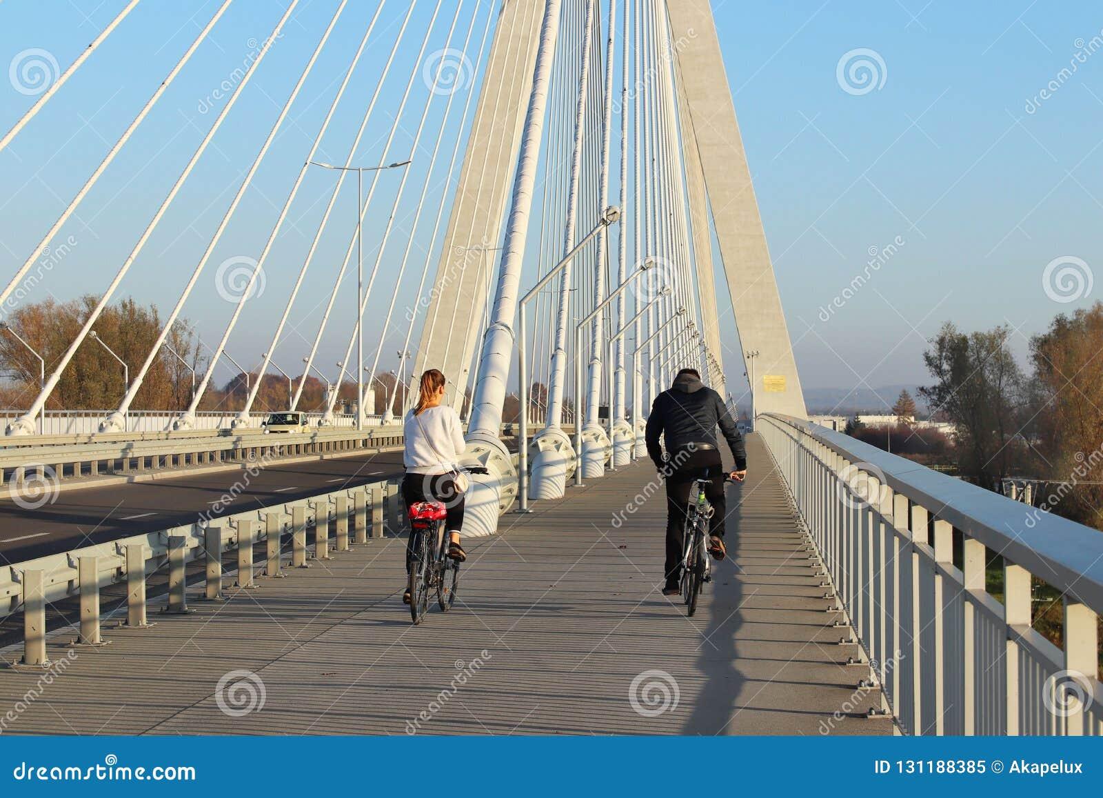 热舒夫,波兰- 9 9 2018年:有女孩乘坐的自行车的一个人在横跨Wislok河的停止路桥梁晴朗的,clea
