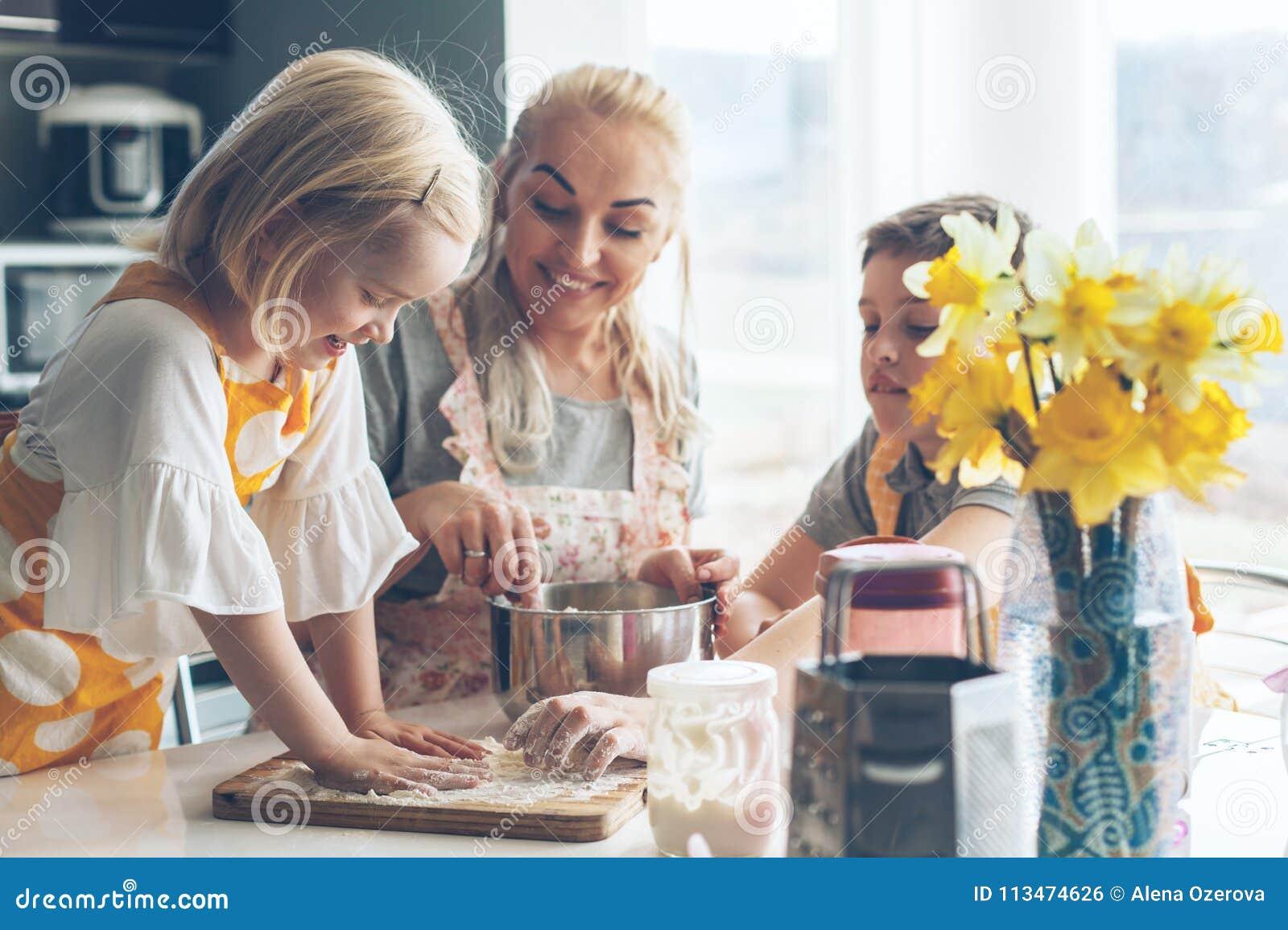 烹调与在厨房的孩子的妈妈