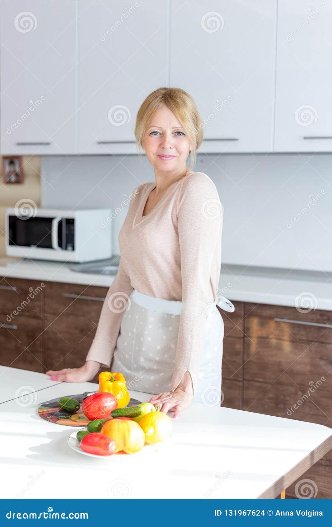 烹调健康食品的资深妇女在房子厨房