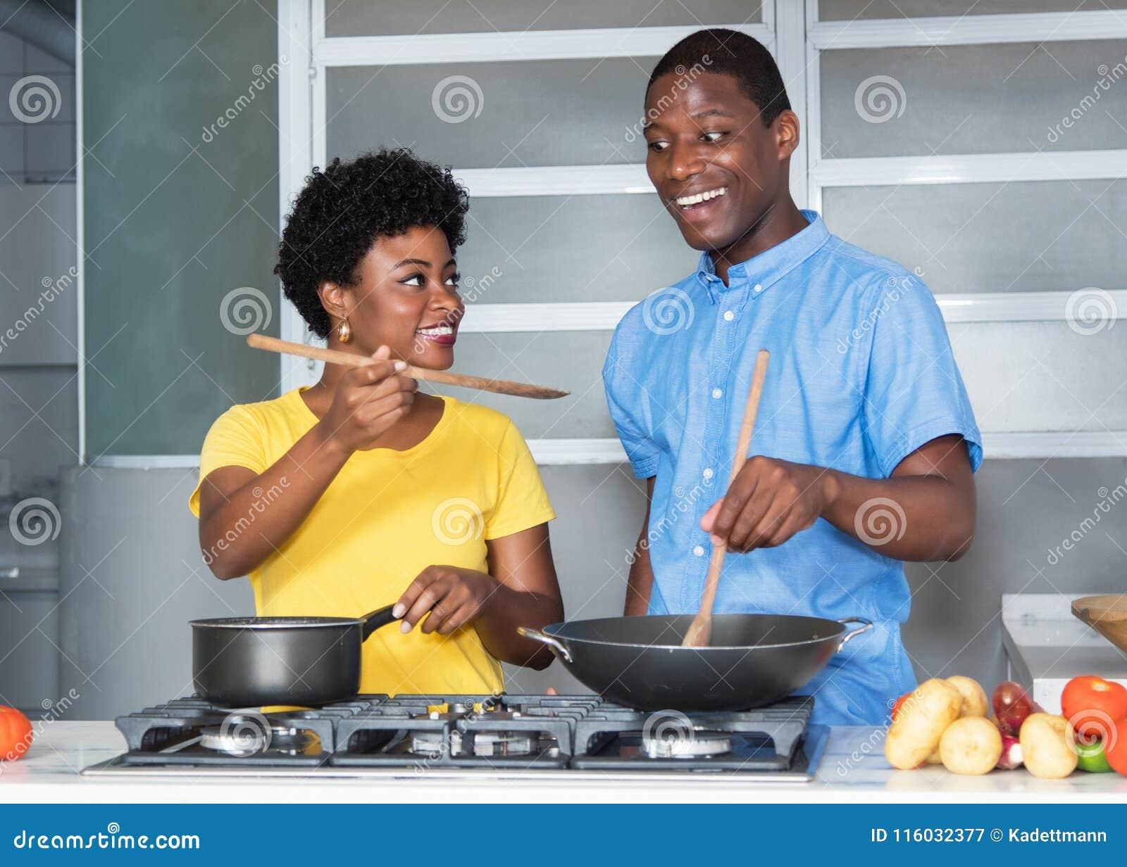 烹调在厨房的非裔美国人的爱夫妇