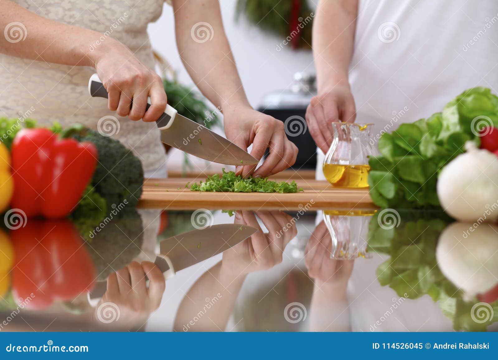 烹调在厨房里的人的手特写镜头  母亲和女儿或者两女性切口蔬菜沙拉或者草本 健康膳食