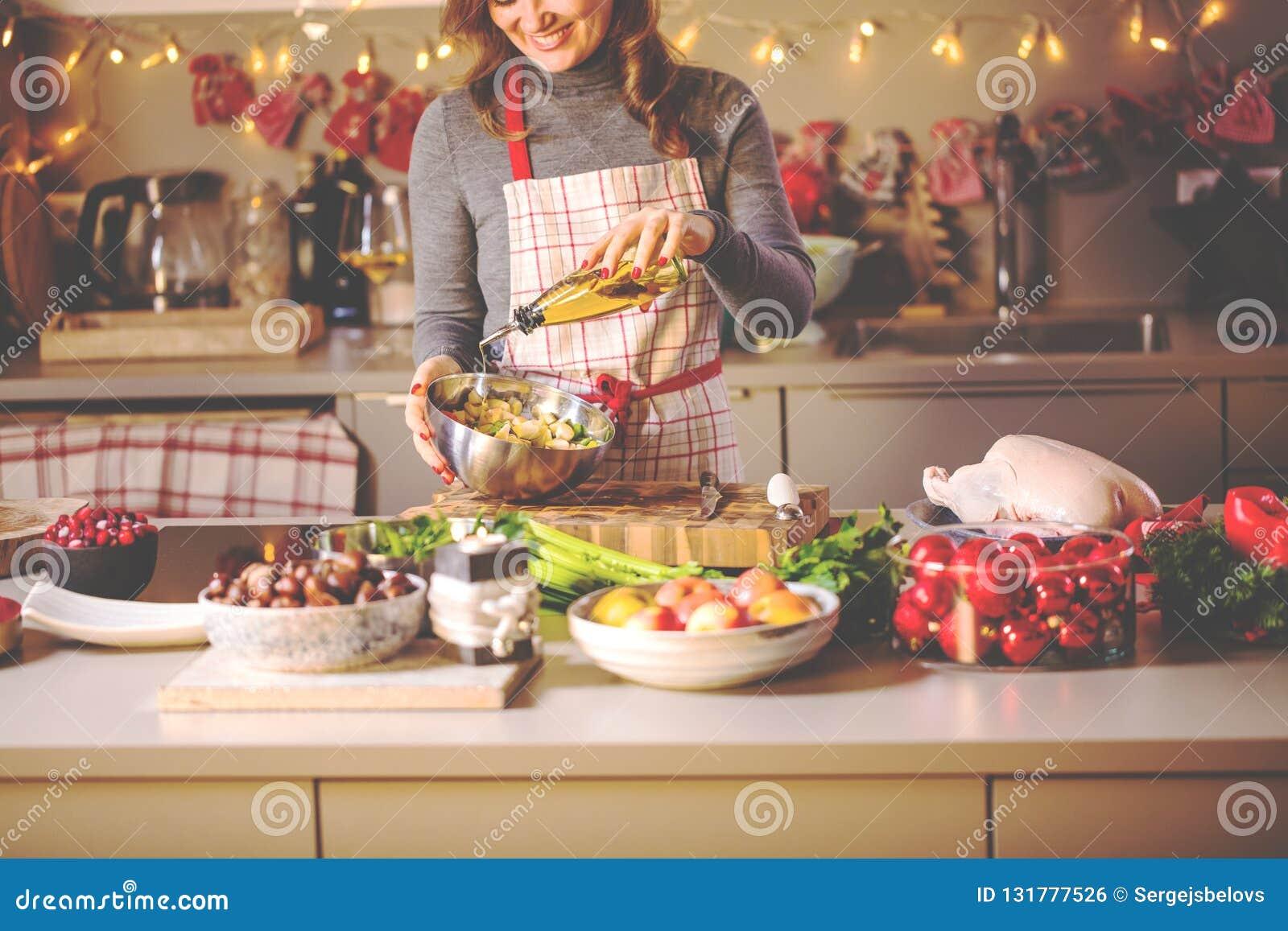烹调在厨房里的少妇 圣诞节被充塞的鸭子或鹅的健康食品