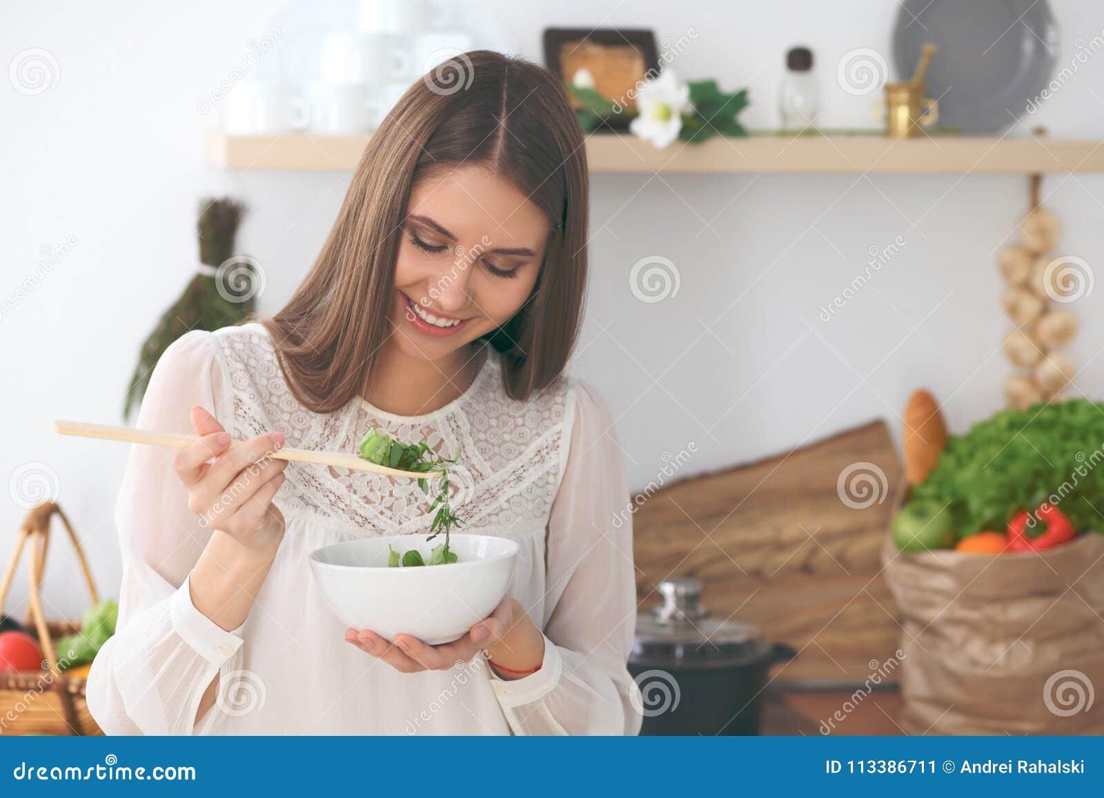烹调在厨房里的年轻愉快的妇女 健康膳食、生活方式和烹饪概念