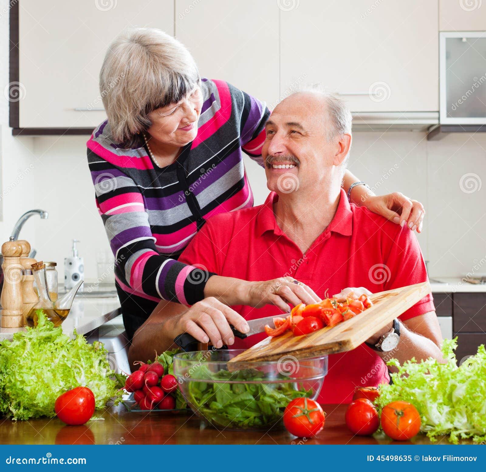 烹调在厨房里的愉快的年长夫妇