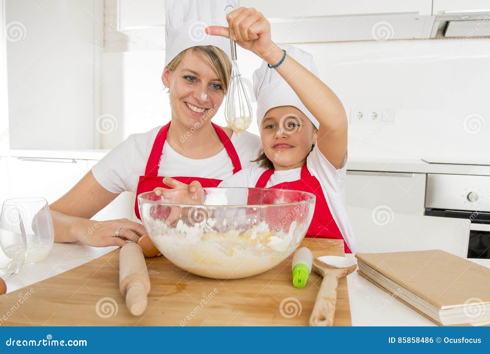 年轻烹调在家一起烘烤的母亲和小甜女儿厨师帽子的和围裙厨房
