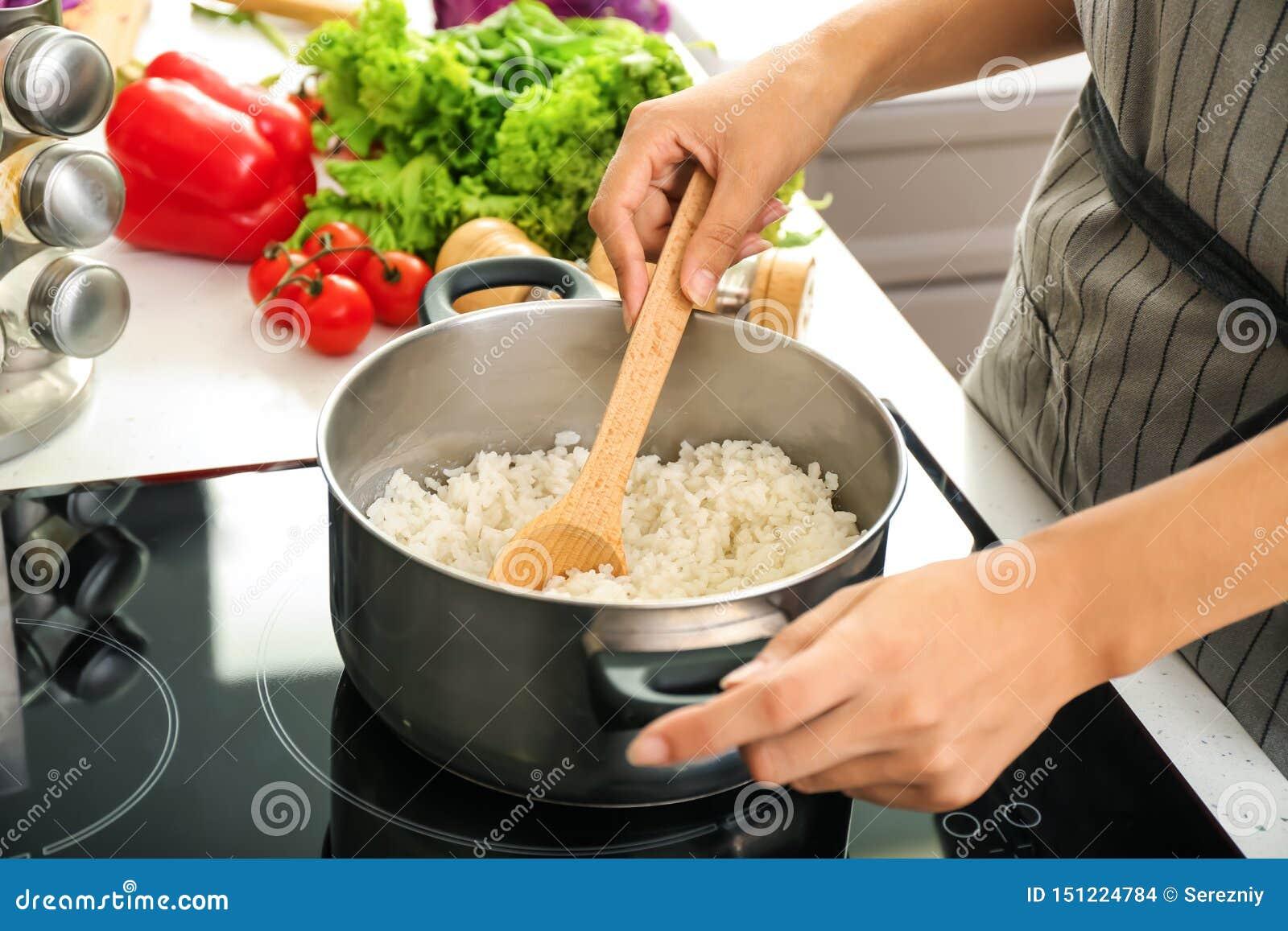 烹调在平底深锅的妇女米在火炉