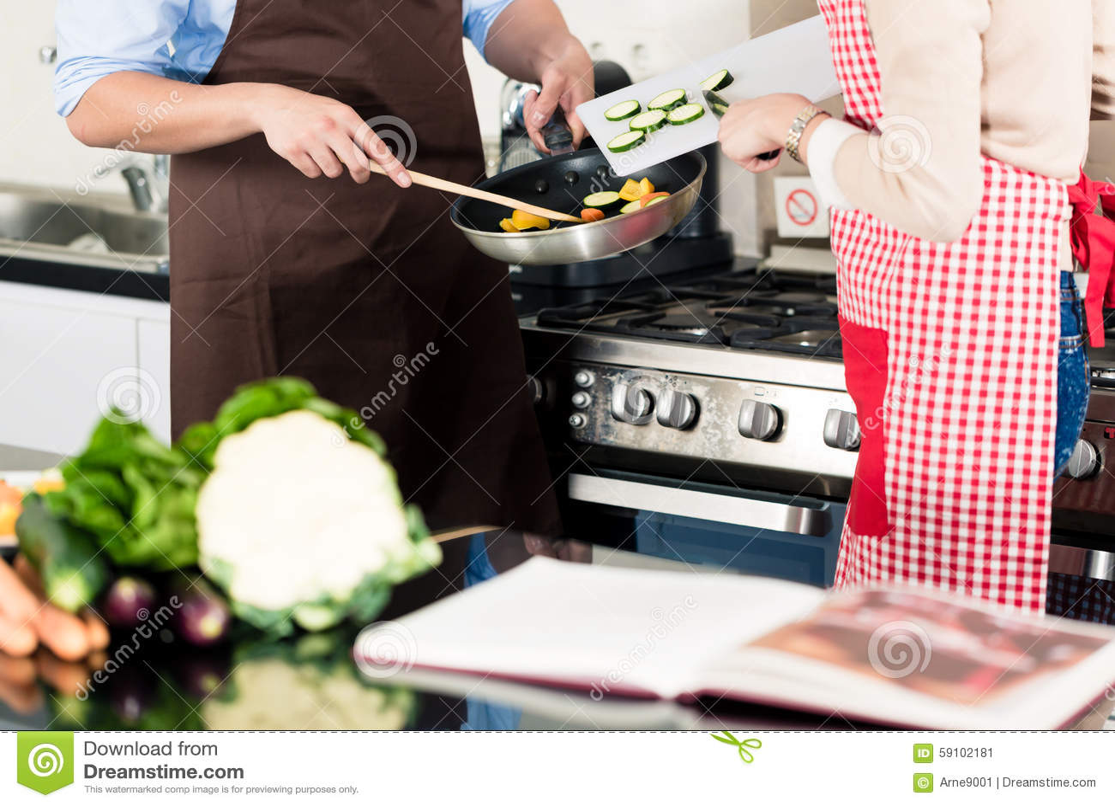 烹调在煎锅的亚洲夫妇菜