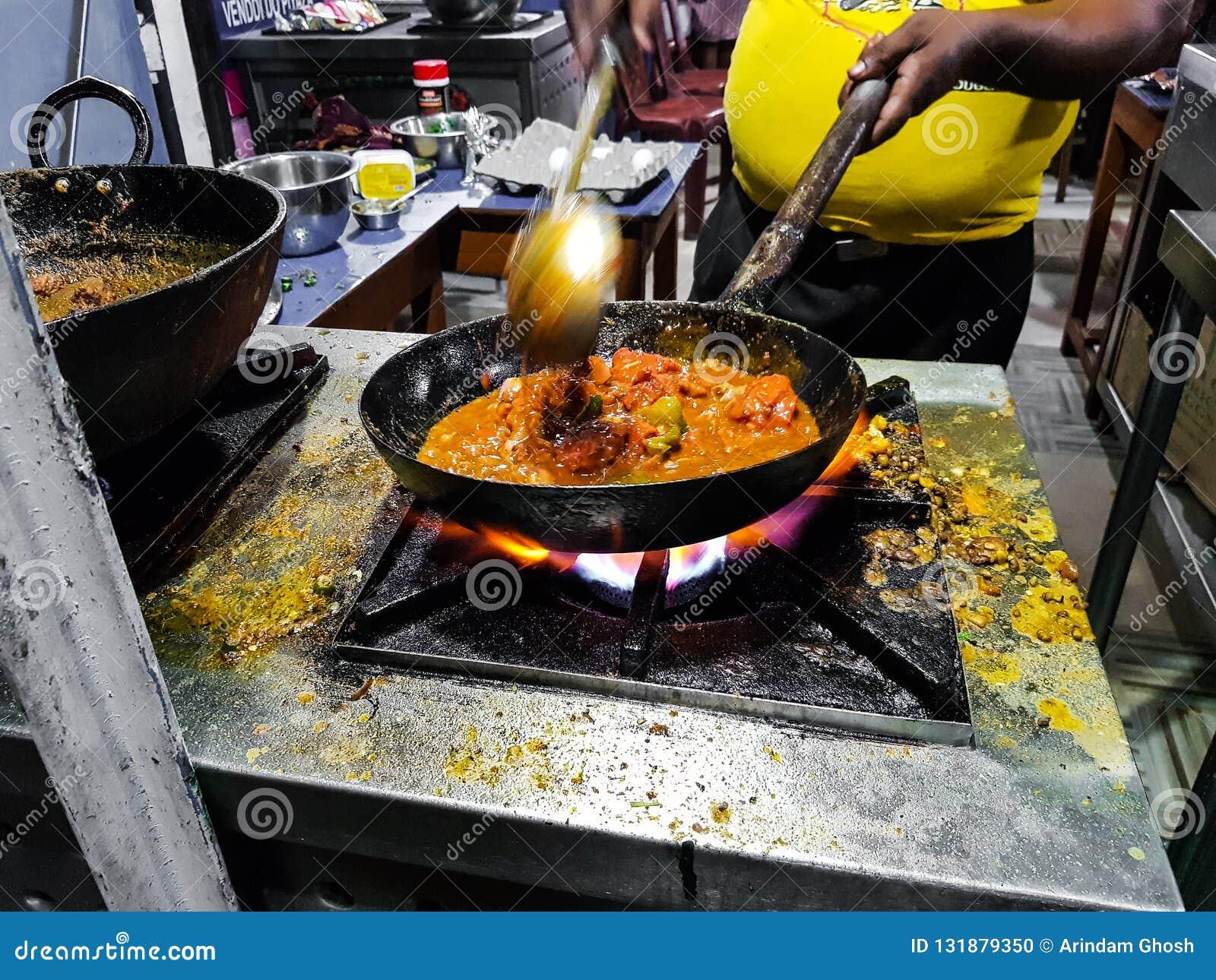 烹调在煎锅的厨师tadka油炸物在一个火炉的一个路边食物角落在火焰