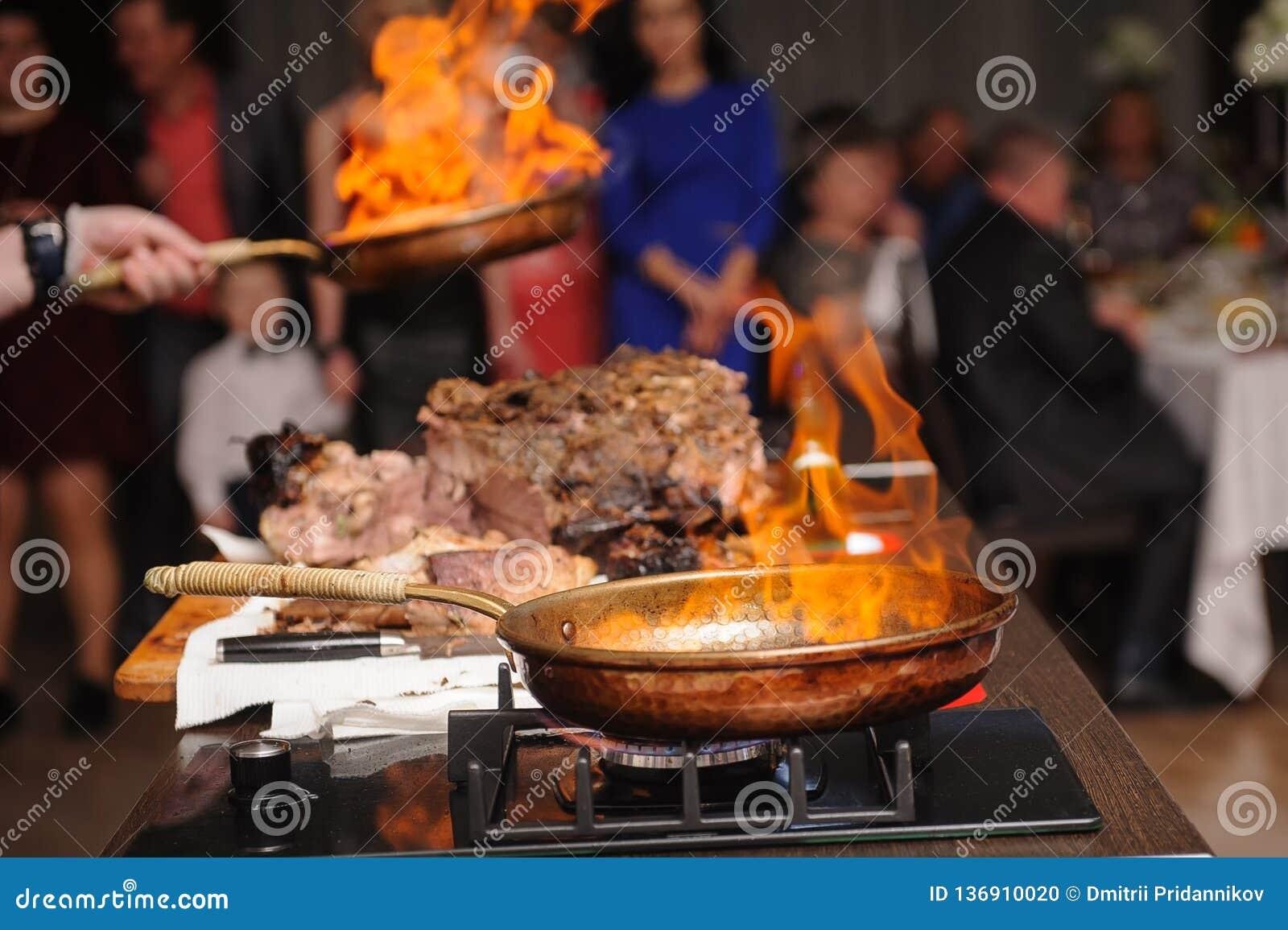 烹调展示,厨师厨师,油煎在一个煎锅的肉有火的