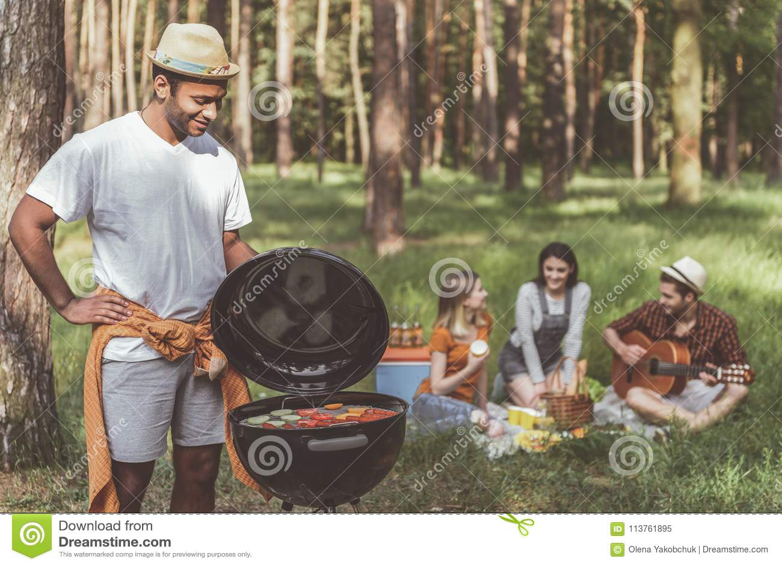 烹调朋友的欢悦人烤肉在森林里