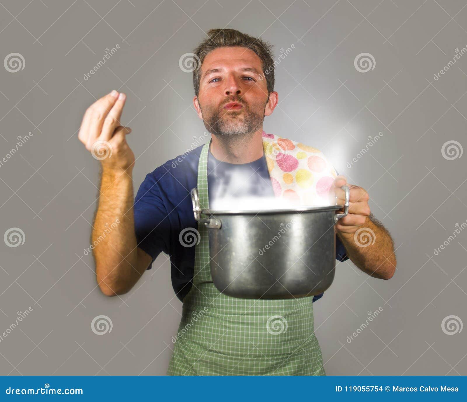烹调汤的年轻可爱的愉快和骄傲的家庭厨师人拿着嗅到膳食芳香打手势欢欣和sa的厨房罐